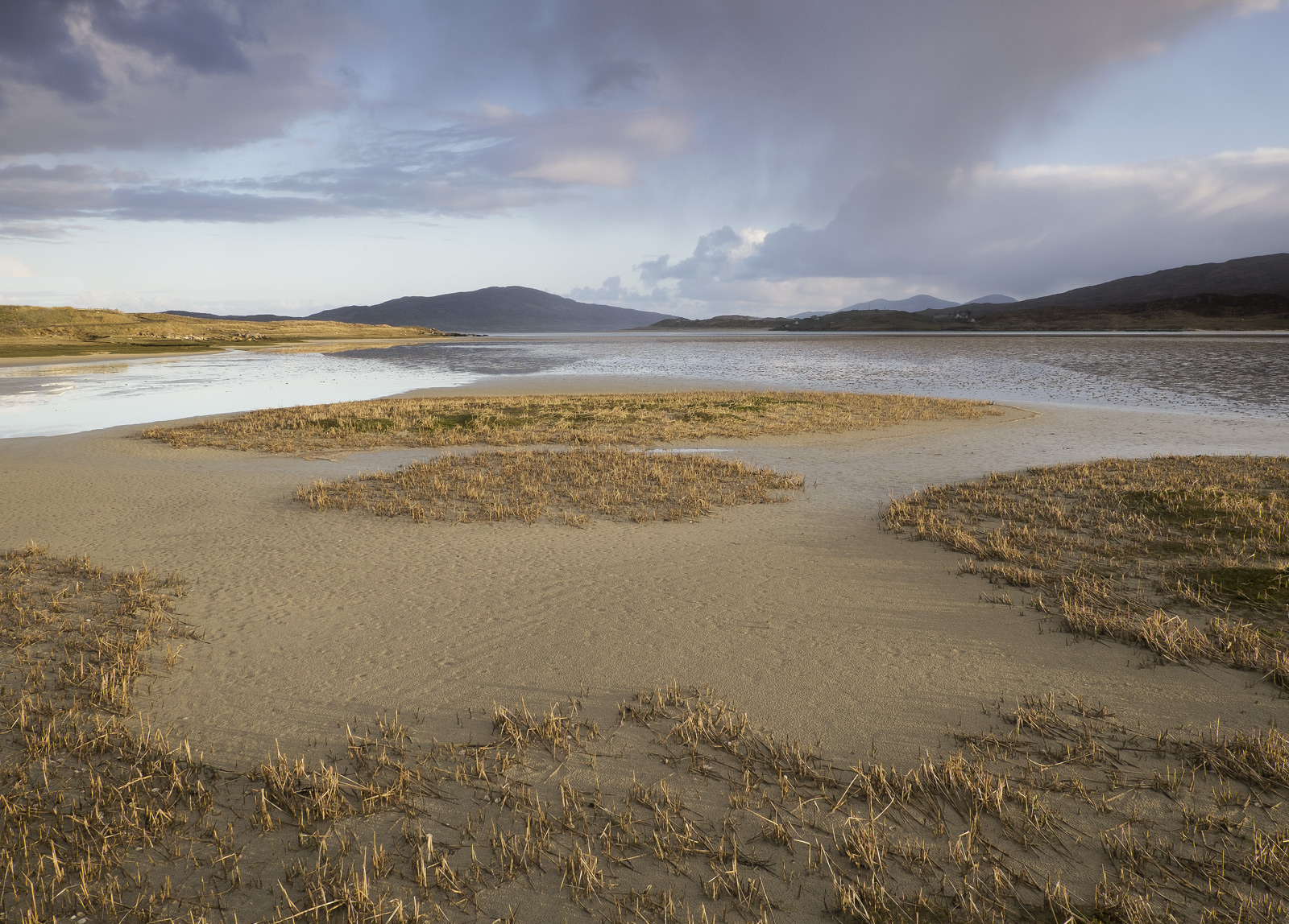 The soft light of a gentle dawn illuminates the sand flats in Luskentyre's massive estuary on a slowly rising tide. Soon...