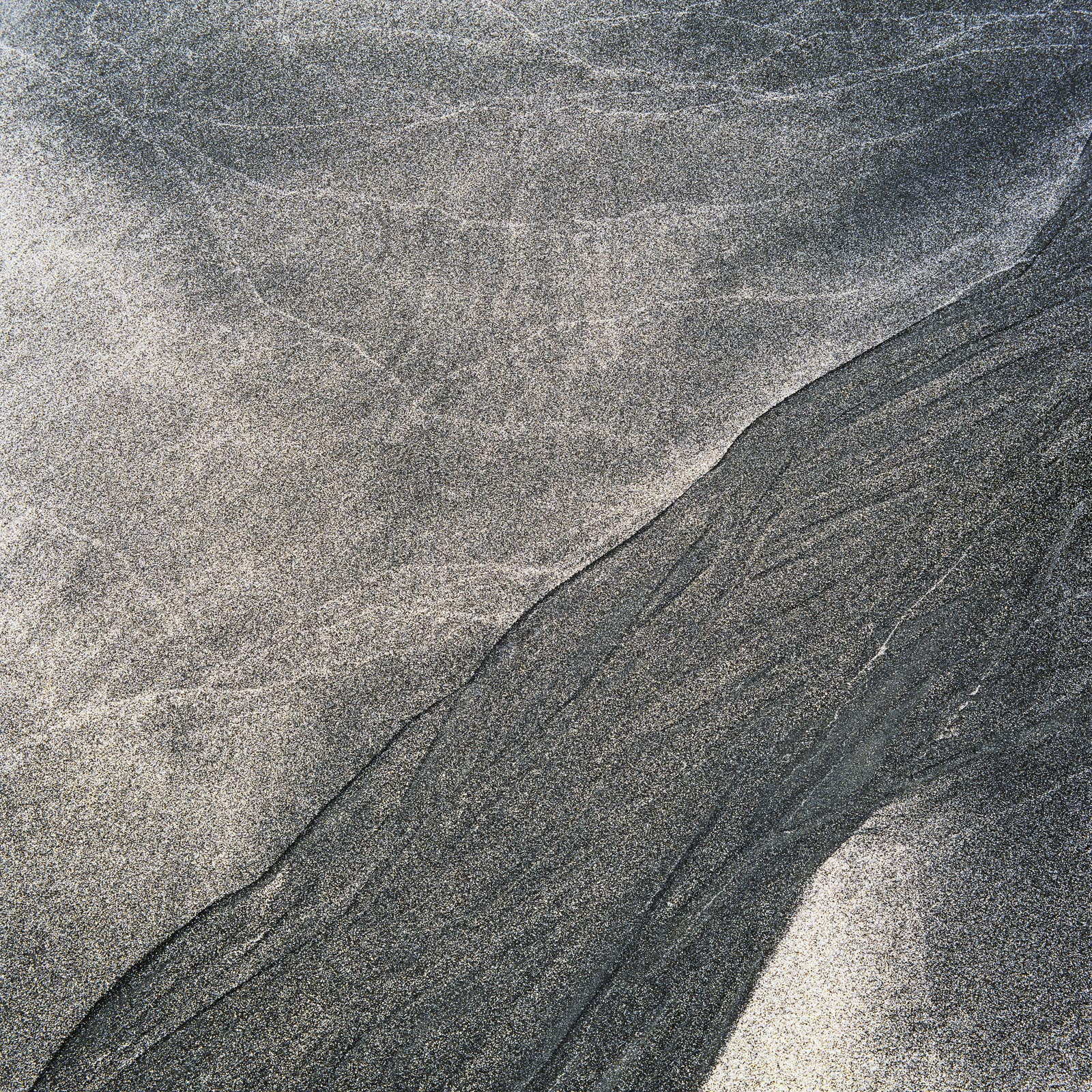 Black and white marbled sand on Staffin's beautiful little beach. The leaching of black rock particles eroded by tide and...