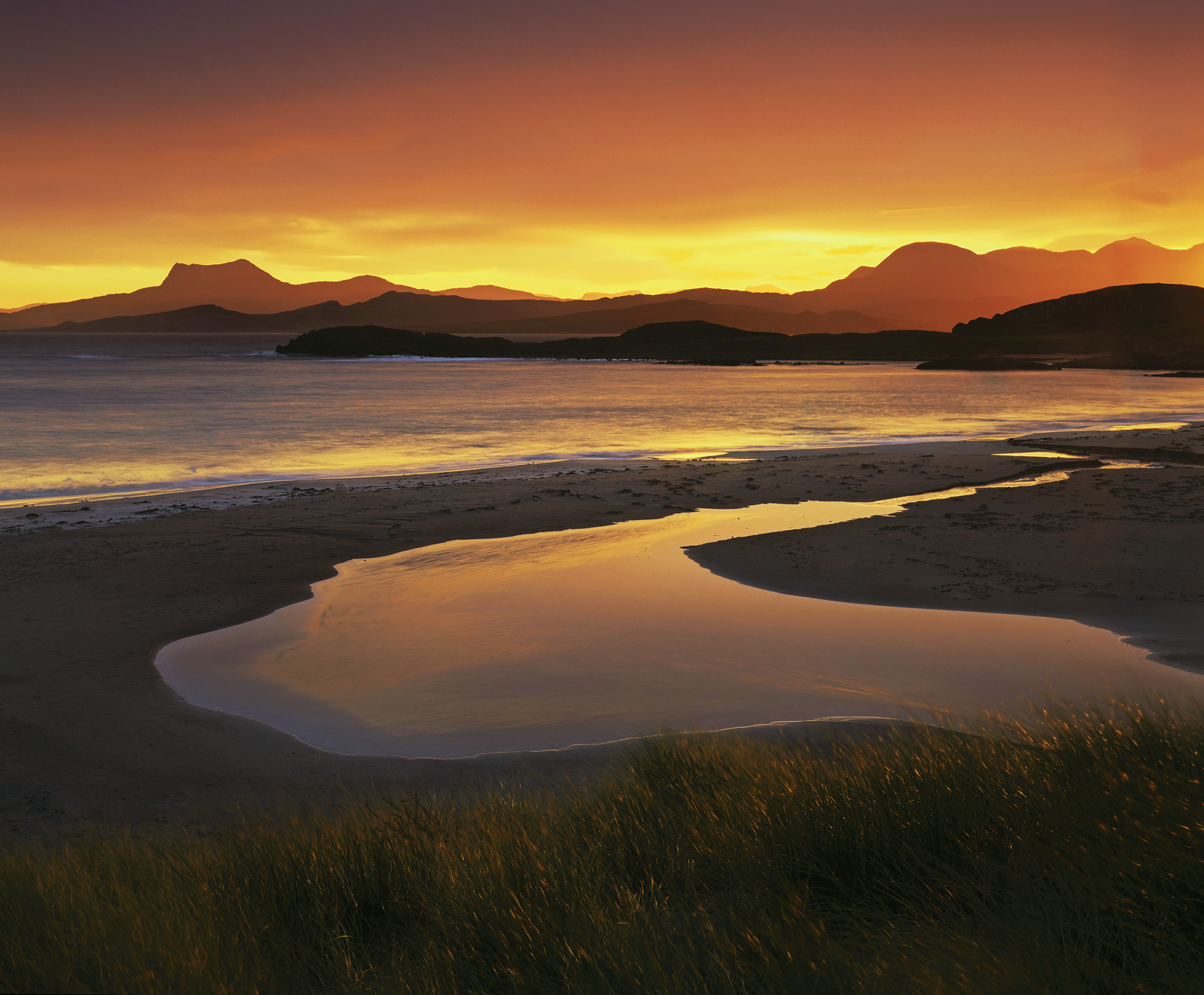 As the sun finally crawled its way over the distant peaks and the intense colour of sunrise over Mellon Udrigle beach started...