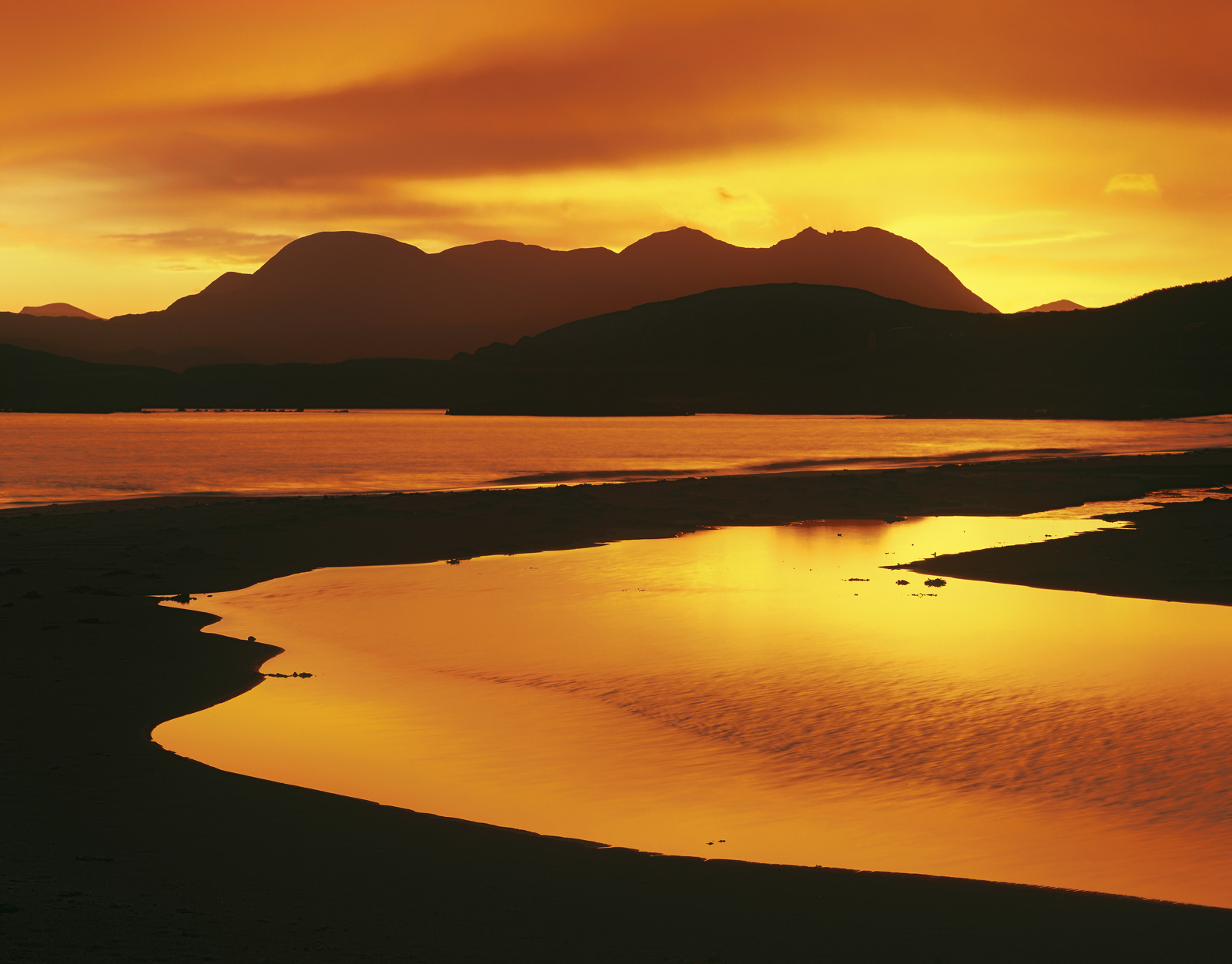 Lava orange skies above the peaks surrounding Mellon Udrigle are reflected in the still waters of a peat stream that meanders...