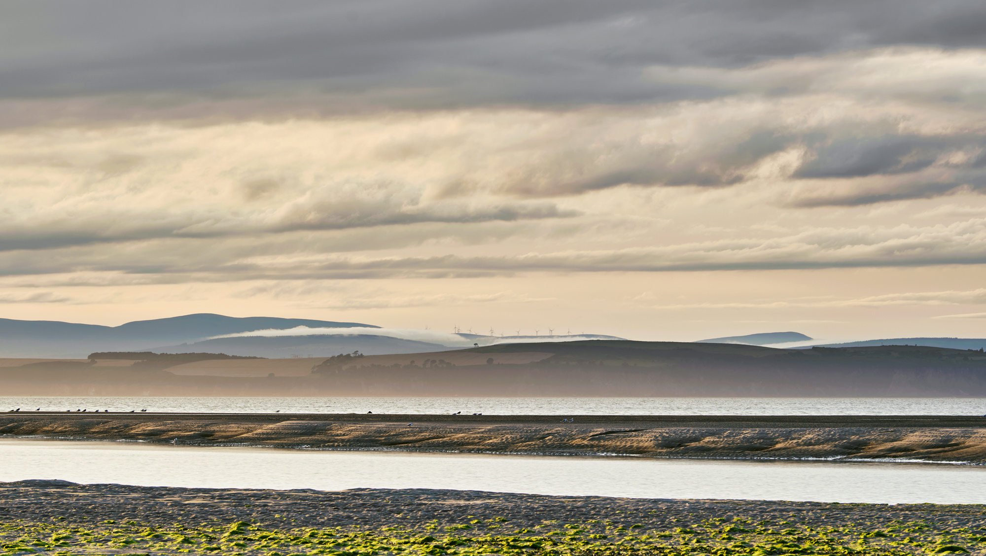 A layered composition of warm summer evening light forming over the Moray Firth and The Maggot near the Highland town of Nairn.