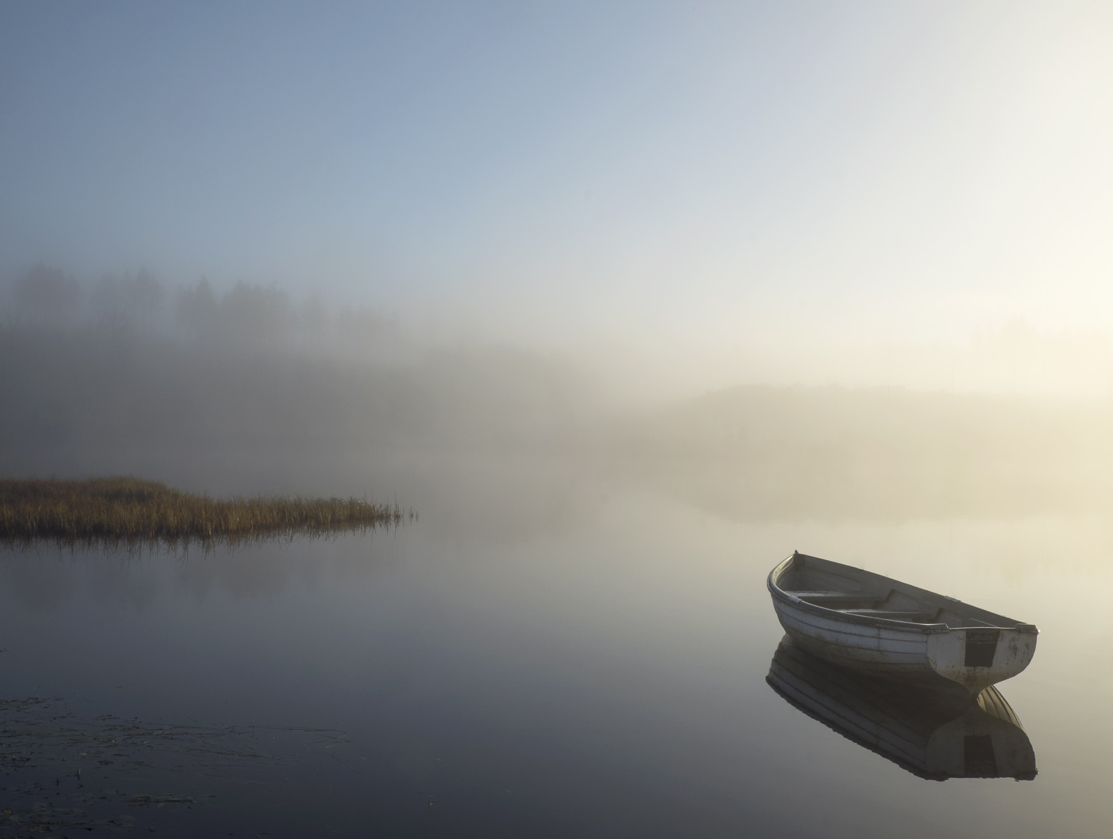 Completely serene a single moored row boat floats in perfect serenity on a mirror of water, mist softly rising from its surface...
