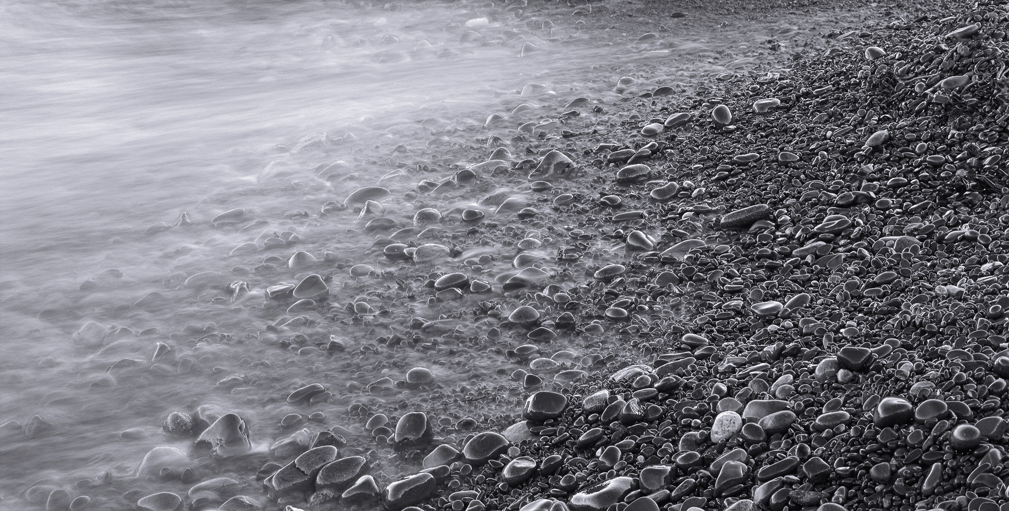 A monochromatic version of the twilight shot molten with the tide rolling over shiny pebbles gleaming bright on one side and...