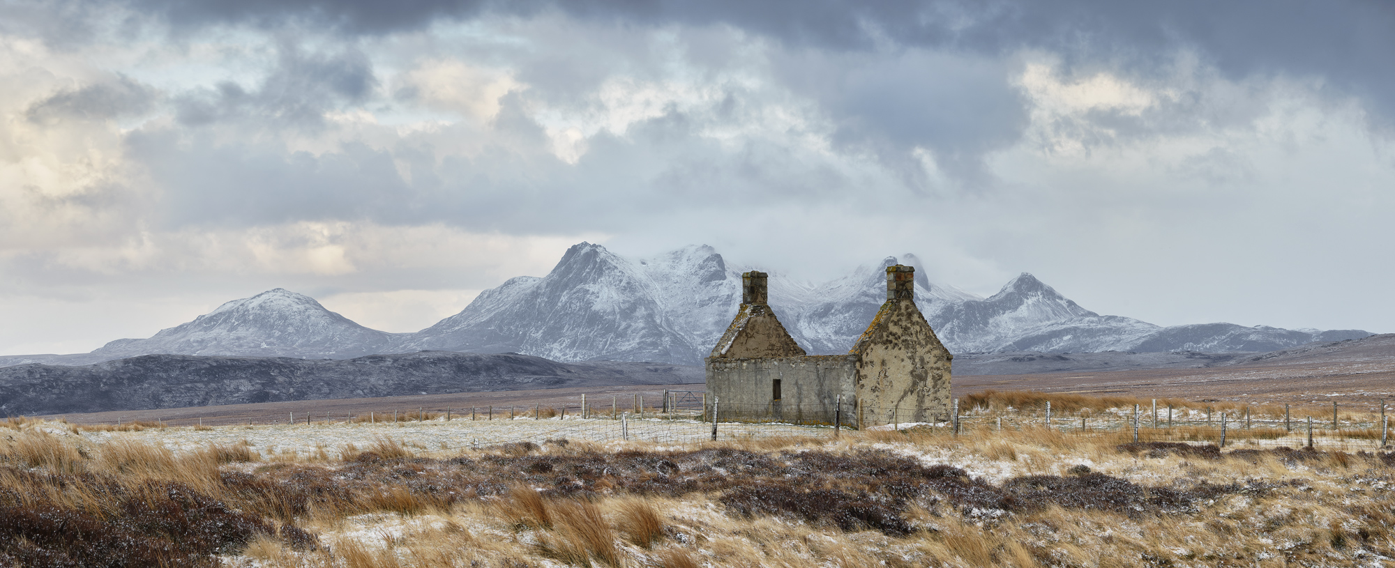 Ruined Moine house high on a bleak moor with snow dusted Ben Loyal Beyond.