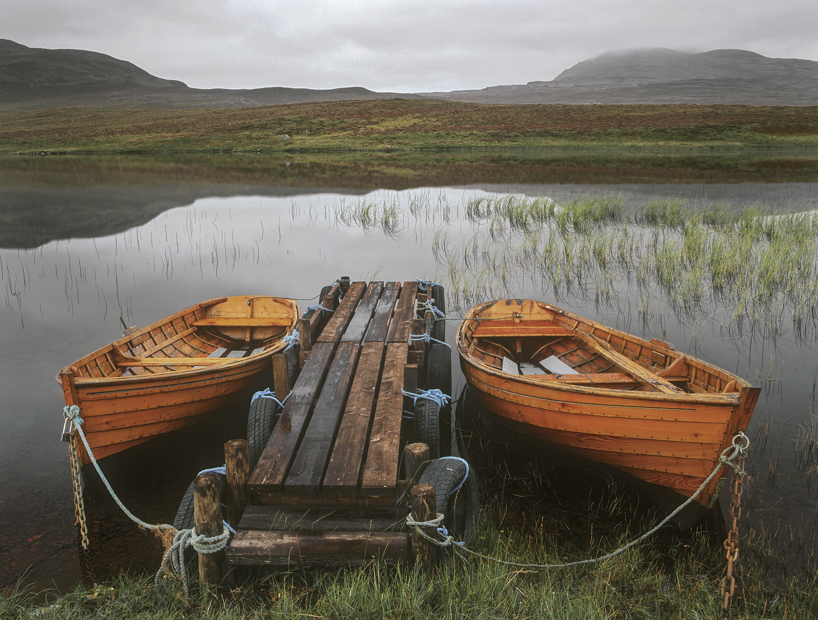 Twin wooden row boats moored together against a wooden gangplank jetty that juts out into a grey and slightly misty Loch Awe.&...