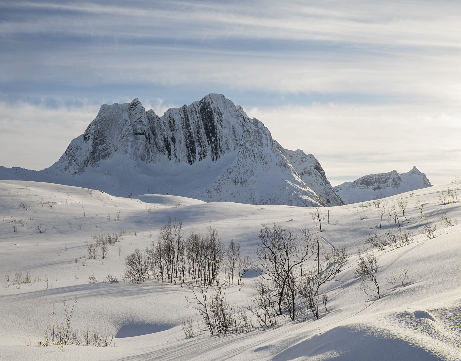 The view across the sunlit snow covered high altitude plains of Eidet toward the imposing peaks of the Senja Island mountains...