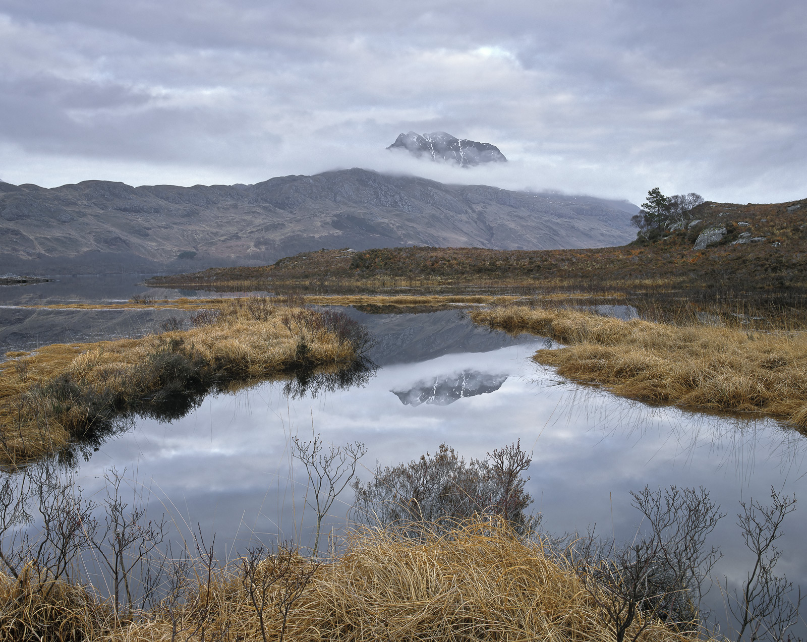 Slioch appears like a careless afterthought from behind a thin veil of cloud and reflects quietly in a mirrored pool nestled...