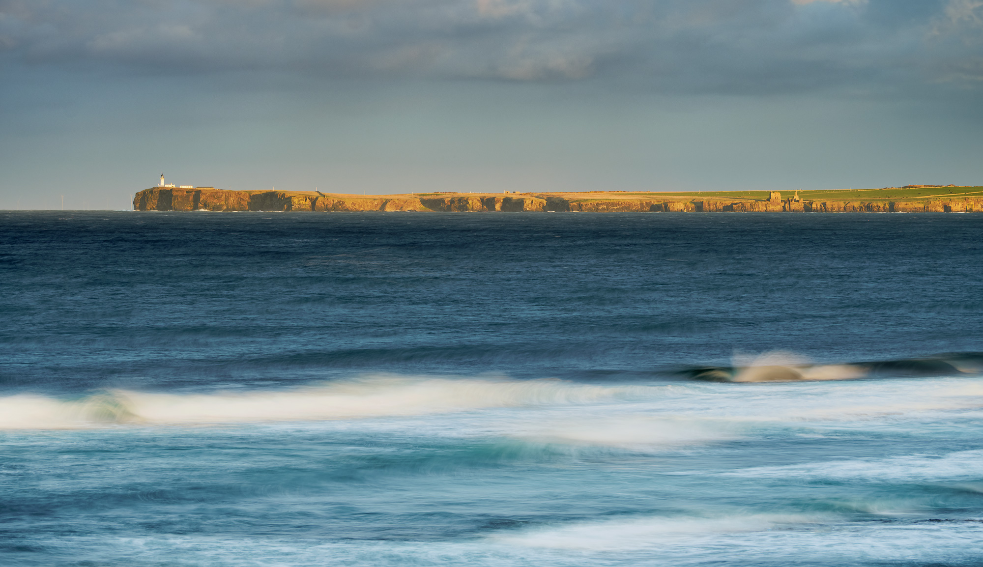 Noss Head lighthouse above a stormy sea at the end of a golden sunlit peninsula as seem from Keiss on the Caithness coast.