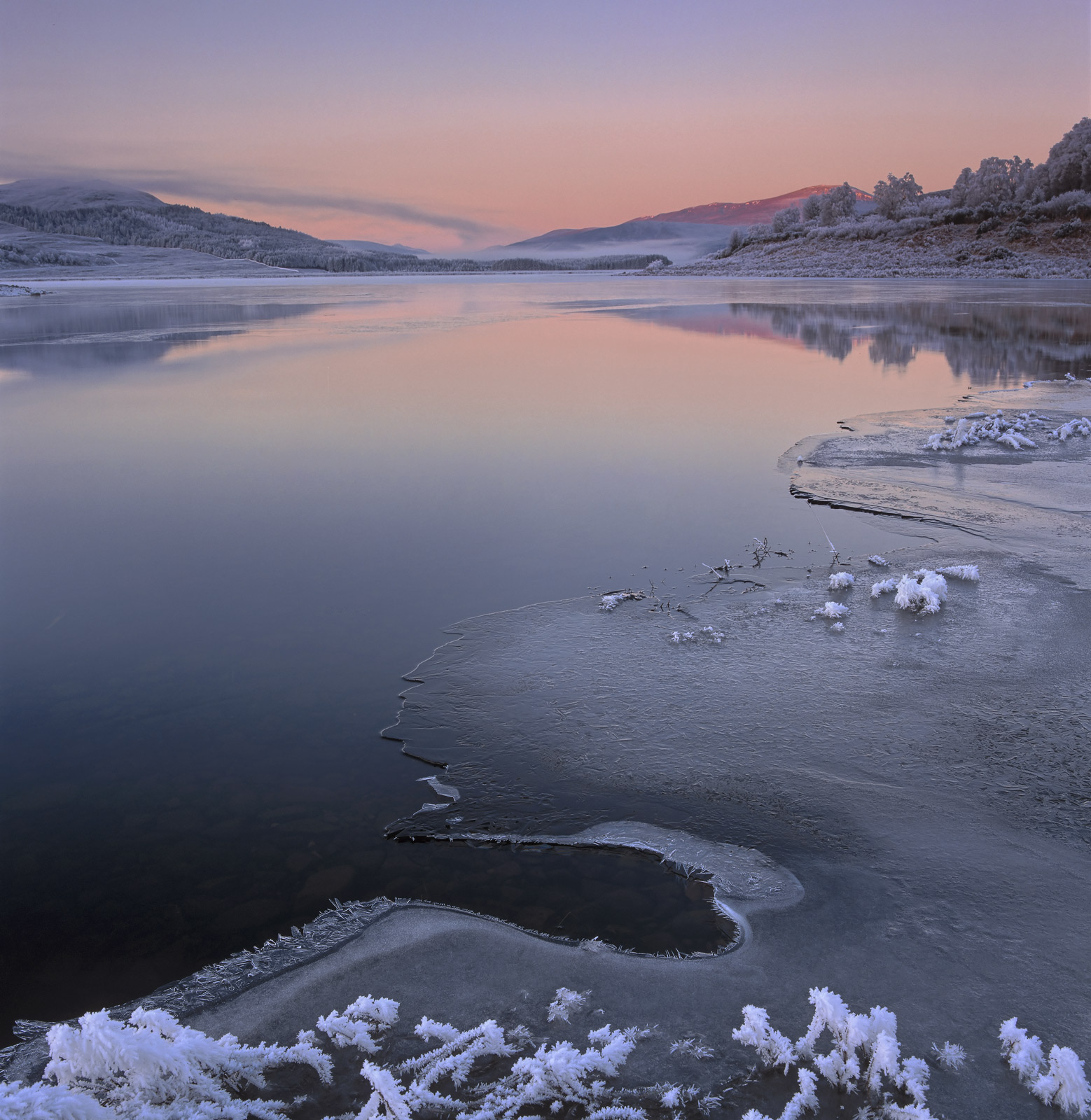 A very beautiful sunrise at Loch Achanalt on a freezing cold morning. The twilight sky slowly rolls back and at the anti...