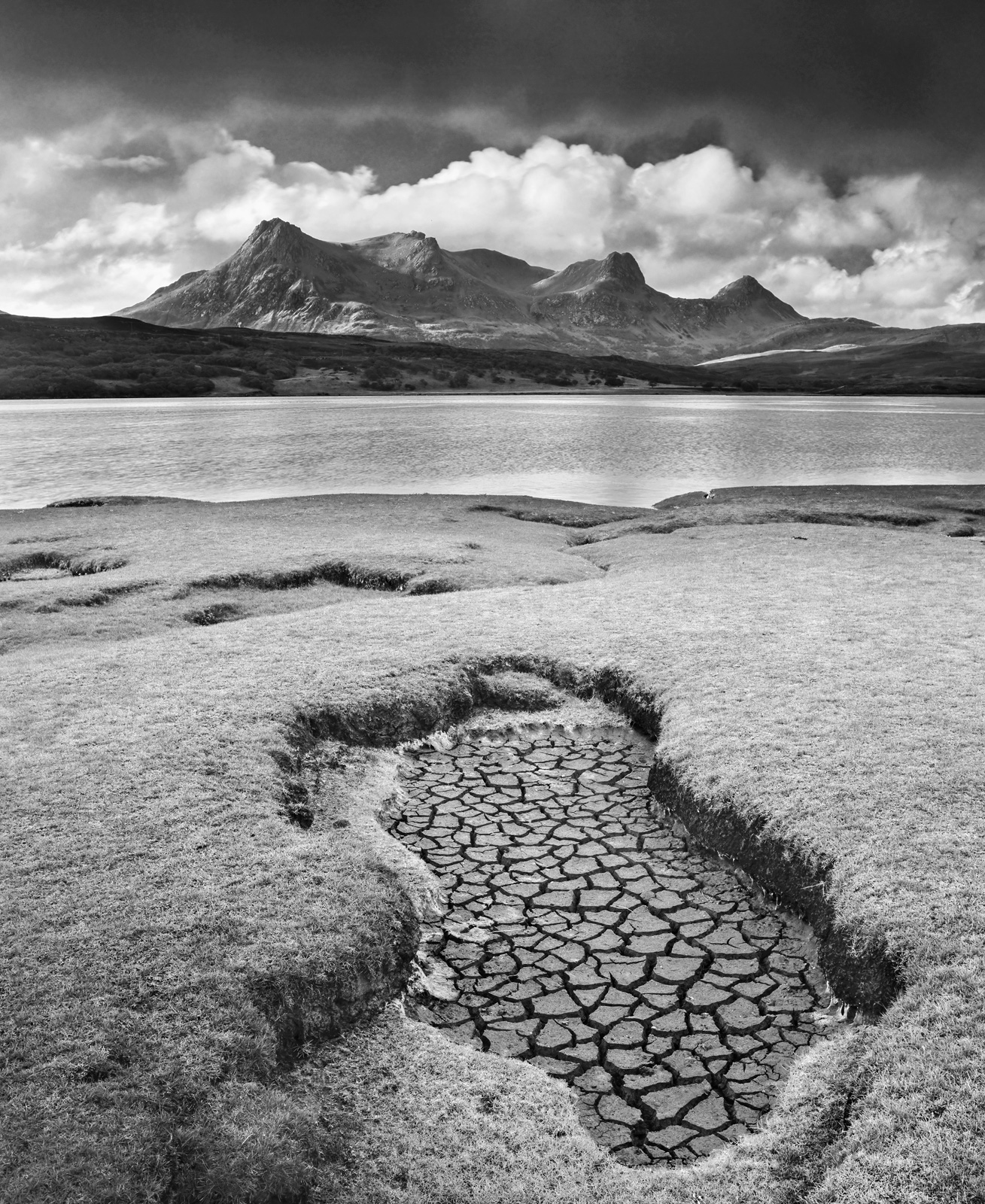 A pool of water has dried on the salt marshes at the edge of the tidal estuary at the Kyle of Tongue. The flakes of cracked...