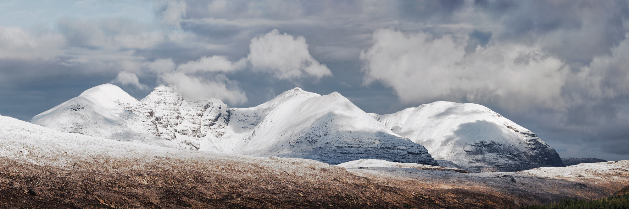 An Teallach snow clad and dappled with light and shade on the high road connecting Braemore Junction with Dundonnell