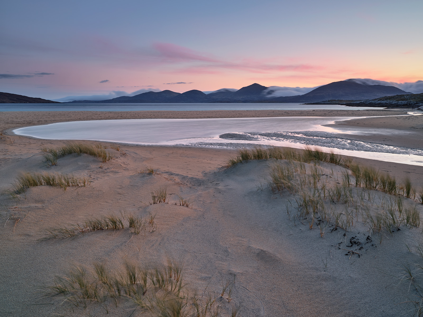 A peachy pink sunrise reflects off the sandy beach and a dune pool at Traigh Rosamol part of Luskentyre Bay on Harris