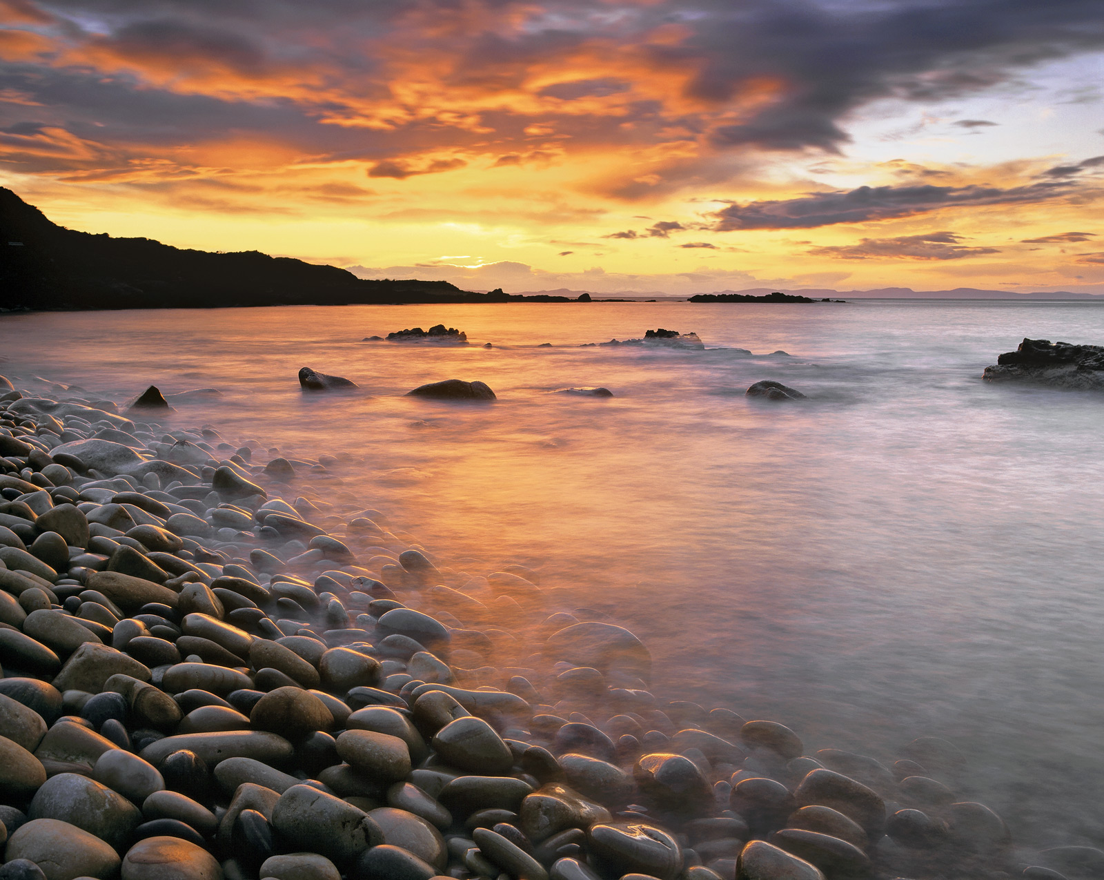 Pebbles cascading down a steep embankment in Cove bay are pale in colour and chatter to each other endlessly as the rough and...