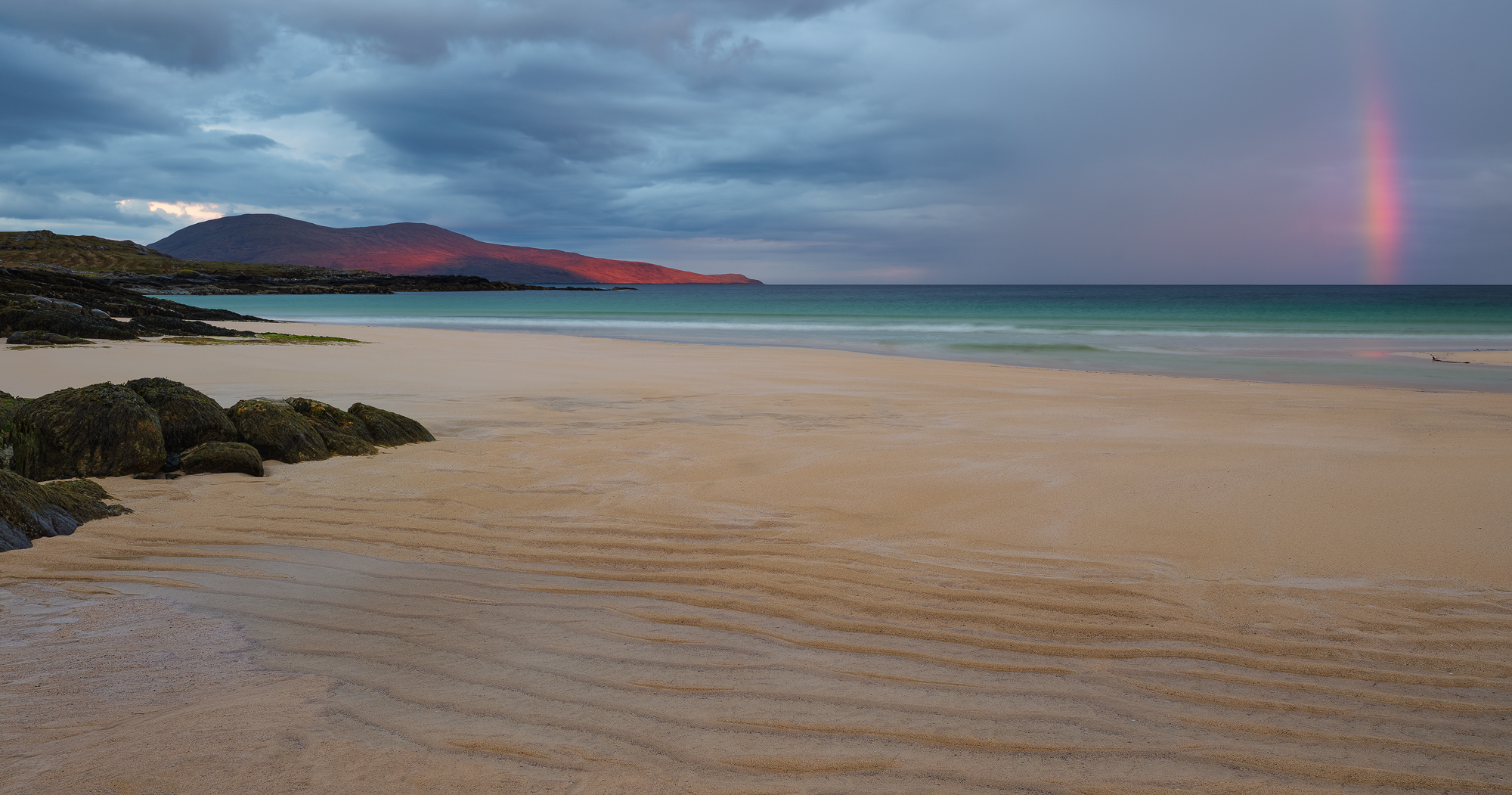 A sunrise rainbow forms over the blood lit Ceapabhal hill and the turquoise sea and the deeply furrowed sandy beach at Traigh Lar on Harris.