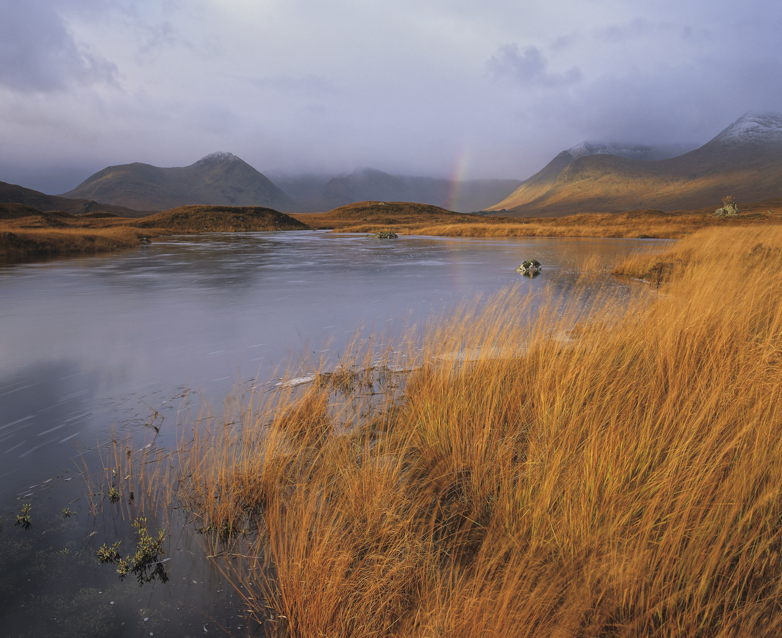 Flaming orange deer grass edge the borders of Loch Na Stainge contrasting with the steely blue of an approaching autumnal storm...
