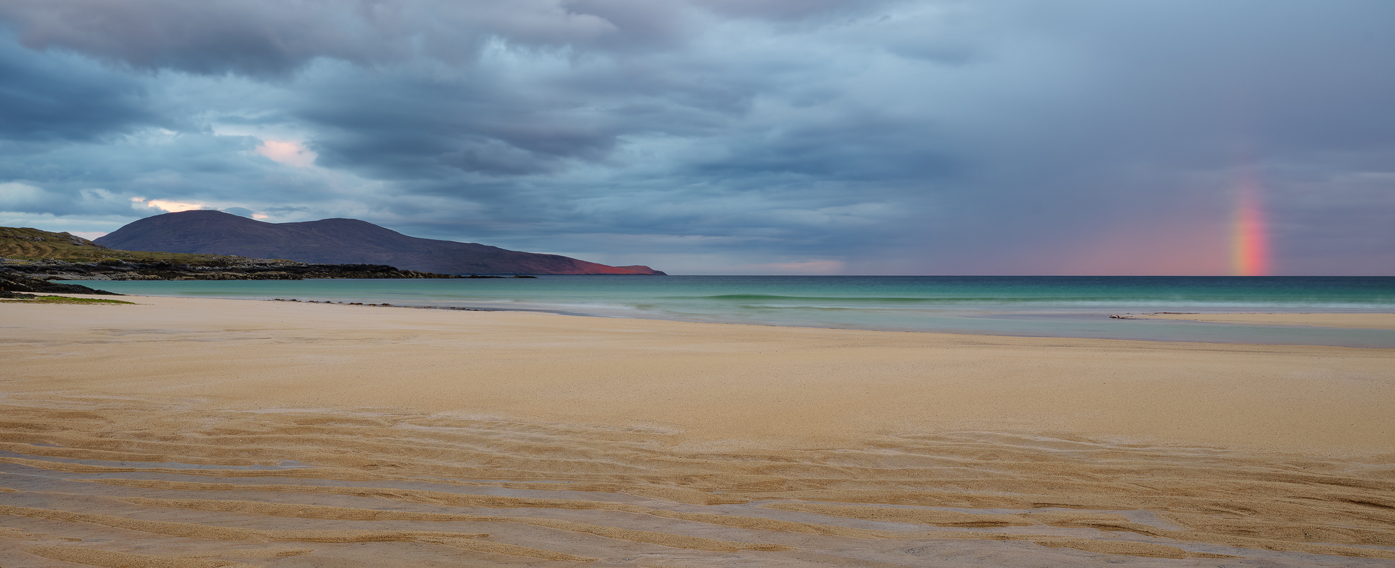 Astonishing red dawn light struck Ceapabhal and formed a brilliant but very shortlived rainbow at Traigh Lar on Harris