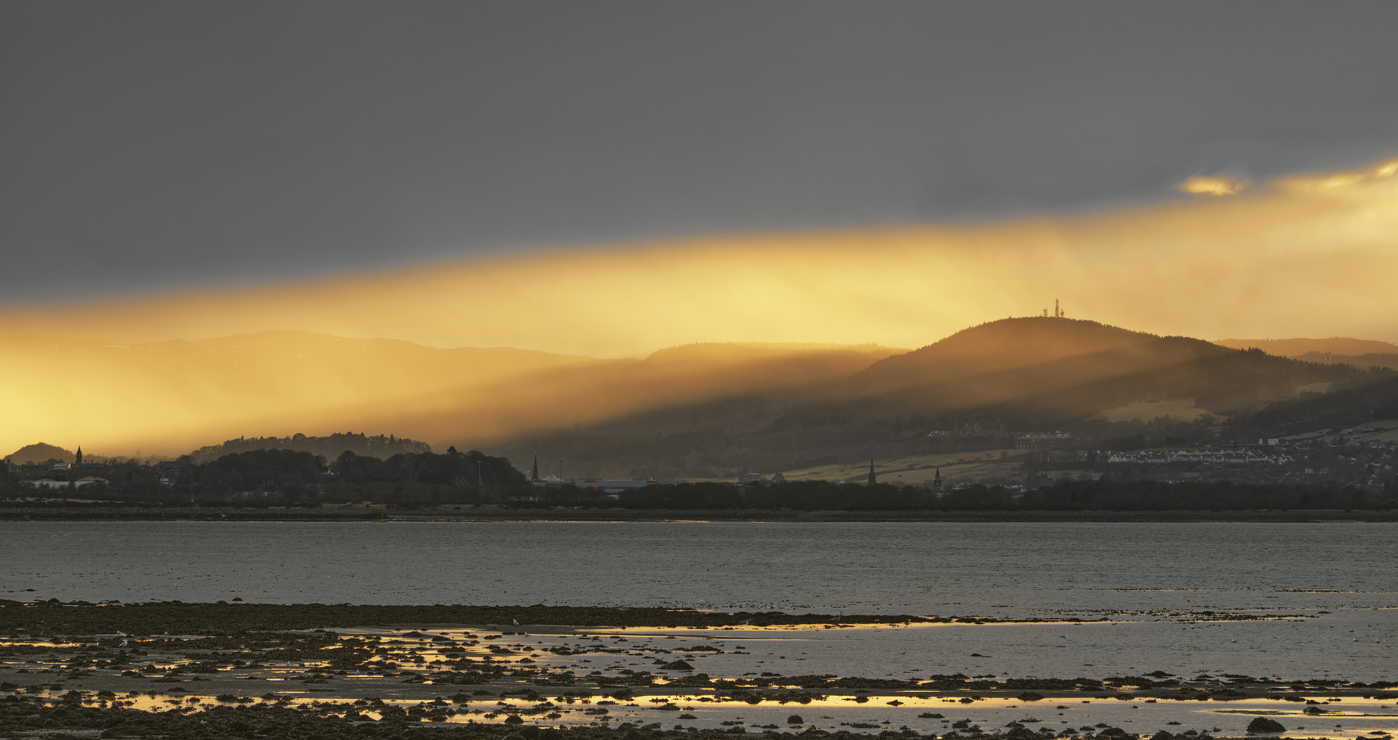 A beam of brilliant and intense golden sunlight blasted a hole through the grey winter clouds and painted the tops of the hills...