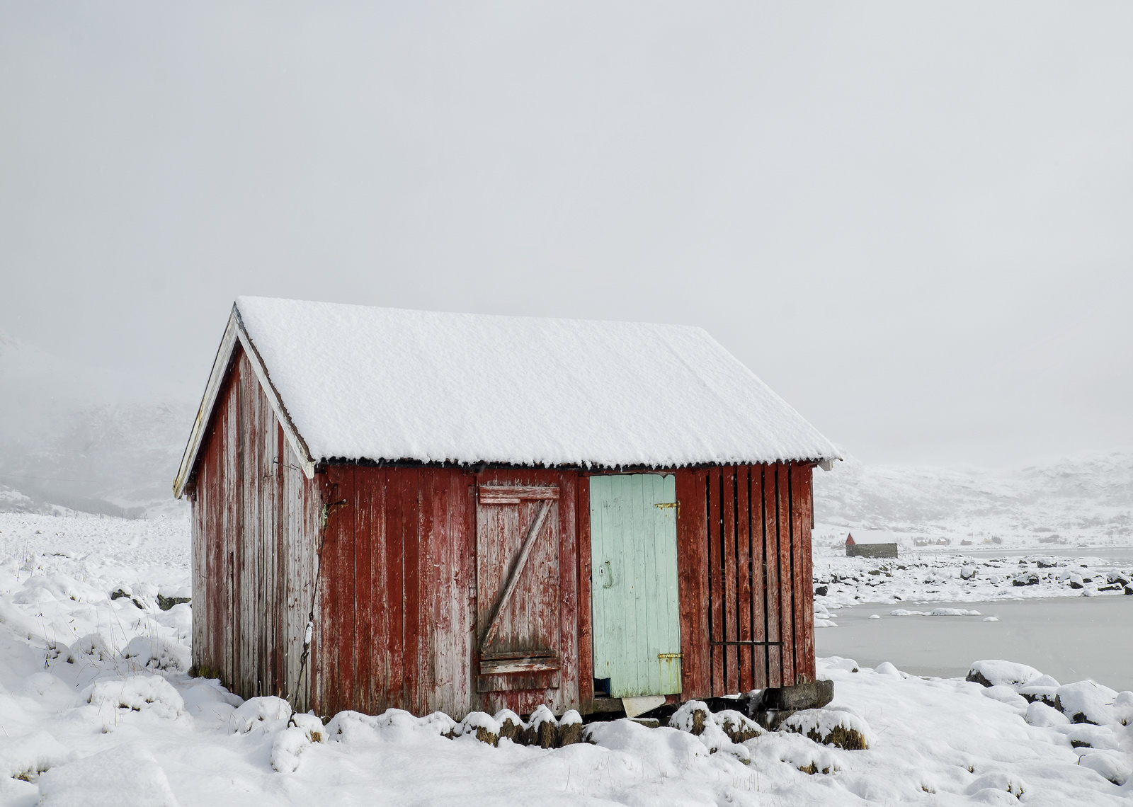An abandoned red shed at the edge of Flakstad Fjord in the hamlet of Bo cuts a stark and lonely sight in the still falling snow...