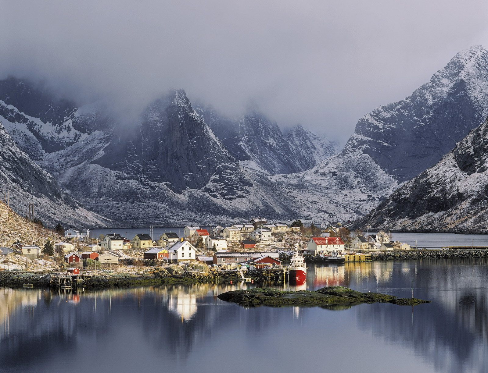 The gloom and blue mood conveyed by the oppressively heavy clouds glowering over the sunlit harbour of Reine was in wonderful...