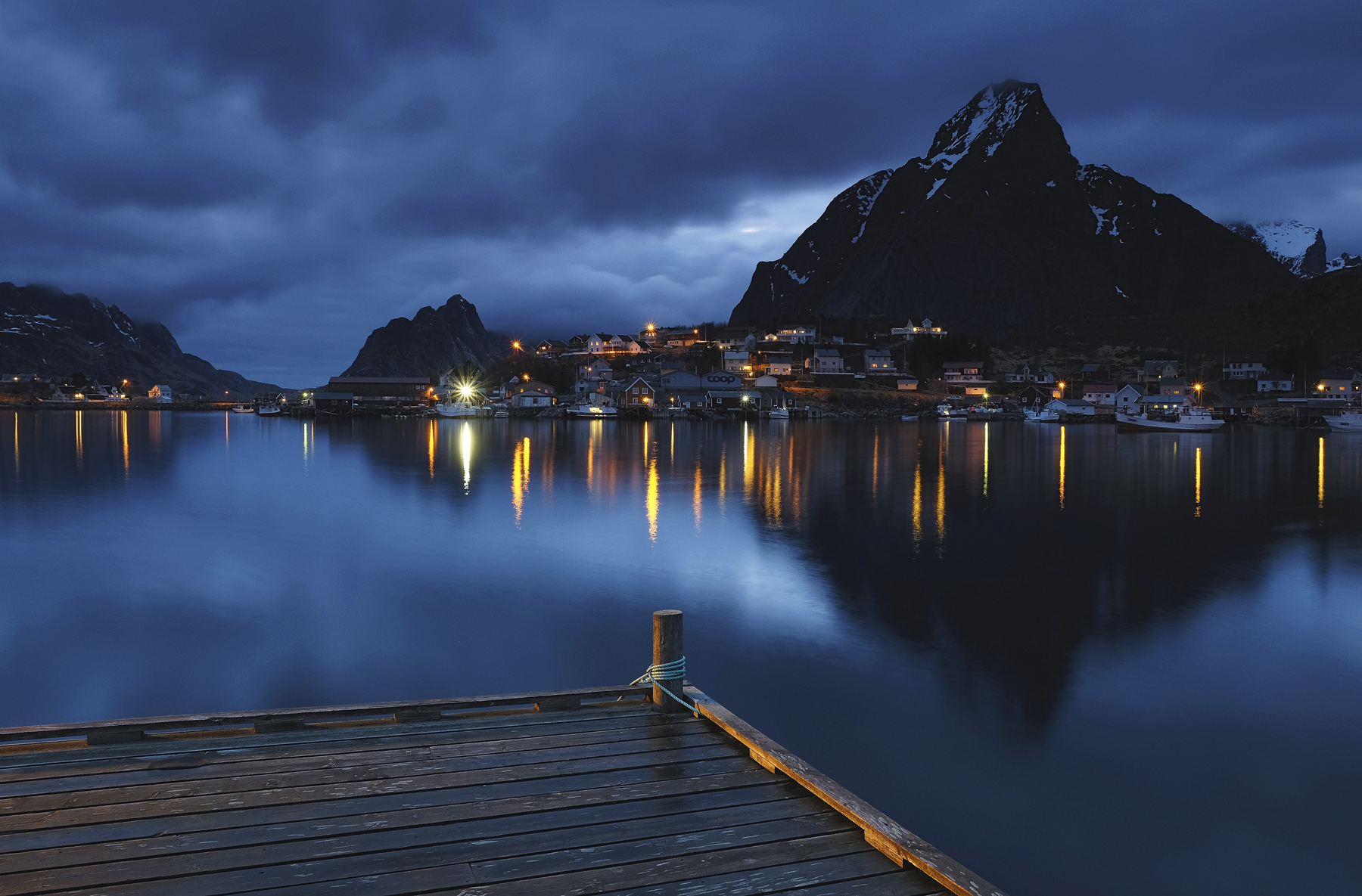 A sumptuous blue twilight on a cloudy evening at Reine harbour jetty with a mix of manmade lighting and ambient light that never...