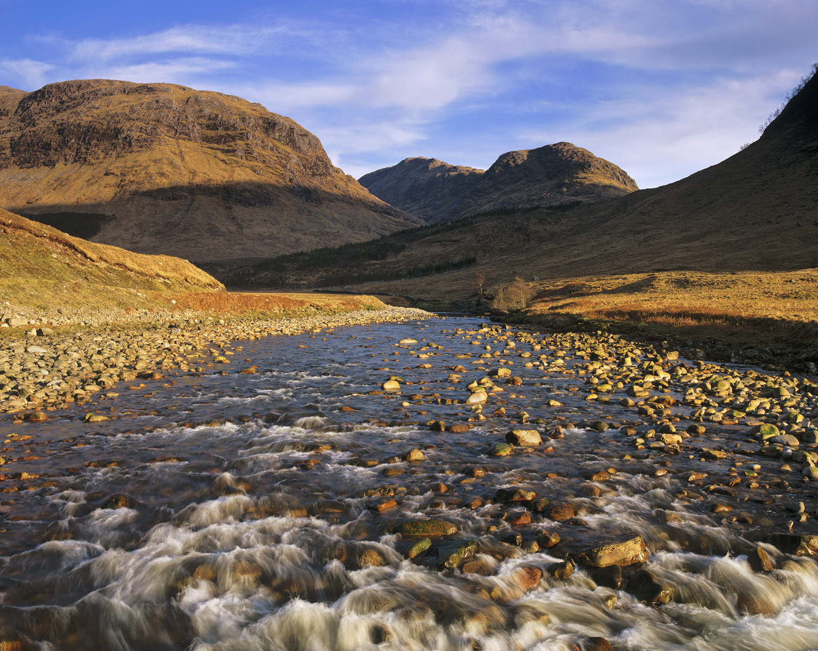 The river Etive spectacularly bounces and tumbles along the Glen Etive valley over red stained rocks and moraine eventually emerging...