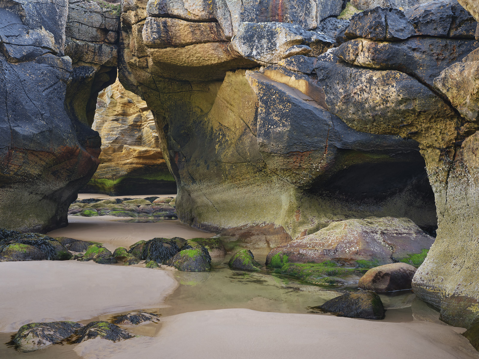 A lovely sculpted sandstone arch next to an equally beautiful sandstone cave at Cove Bay on the Moray coast at dusk.