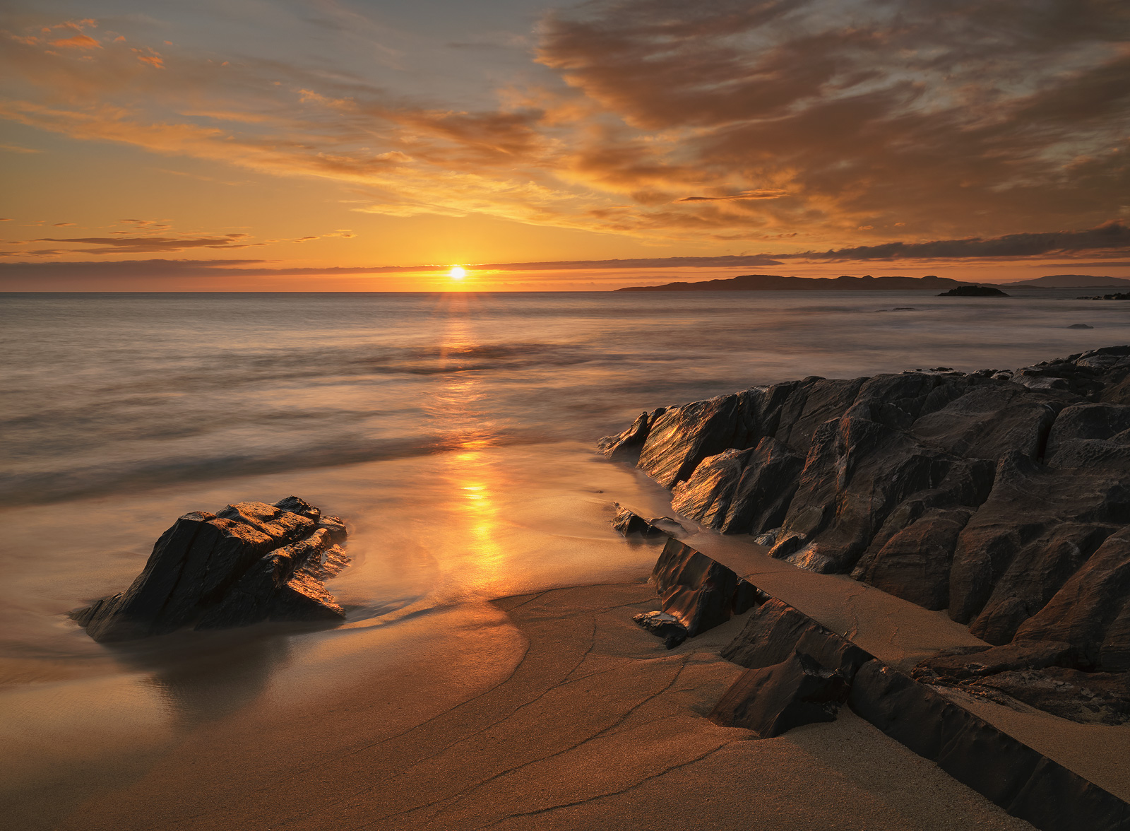 Intense orange light from a satsuma sunset reflects off the orange sand beach and caramelised rocks at Traigh Mhor beach on Harris.