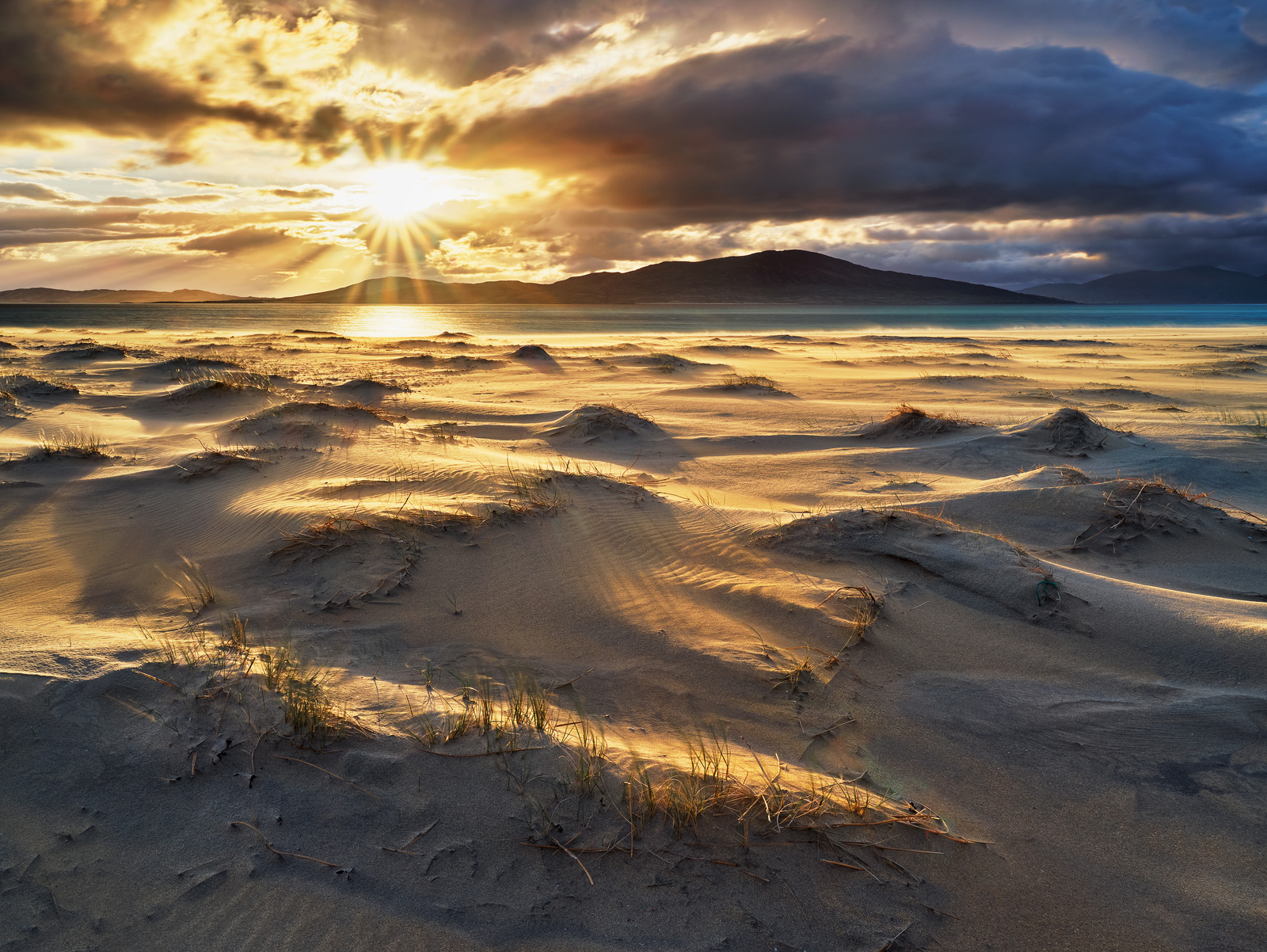 Brilliant low angle light glances the tops of the windblown sand beds on Seilebost beach, Harris