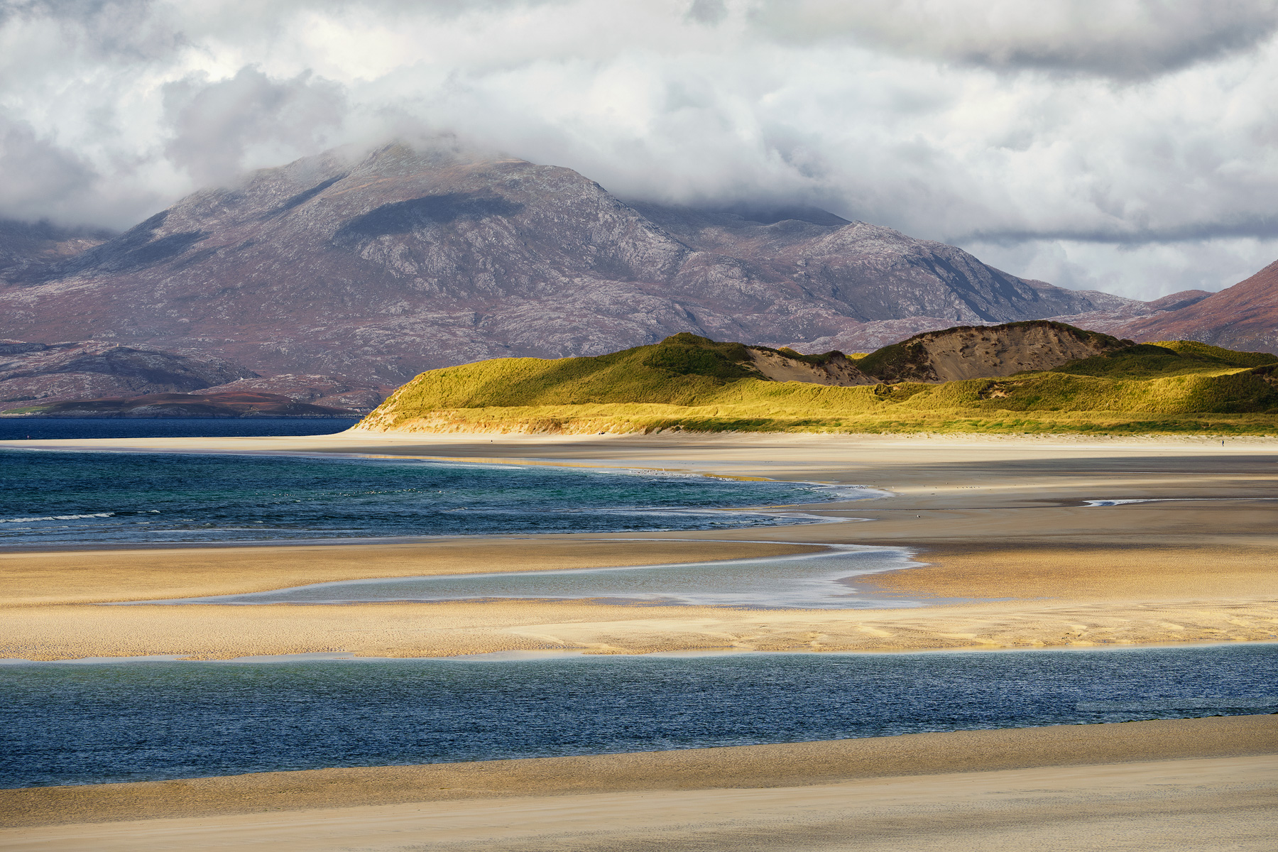 A long lens is used to compress the mountain backdrop of the Harris peaks and the multitude of lines formed by the rising tide...