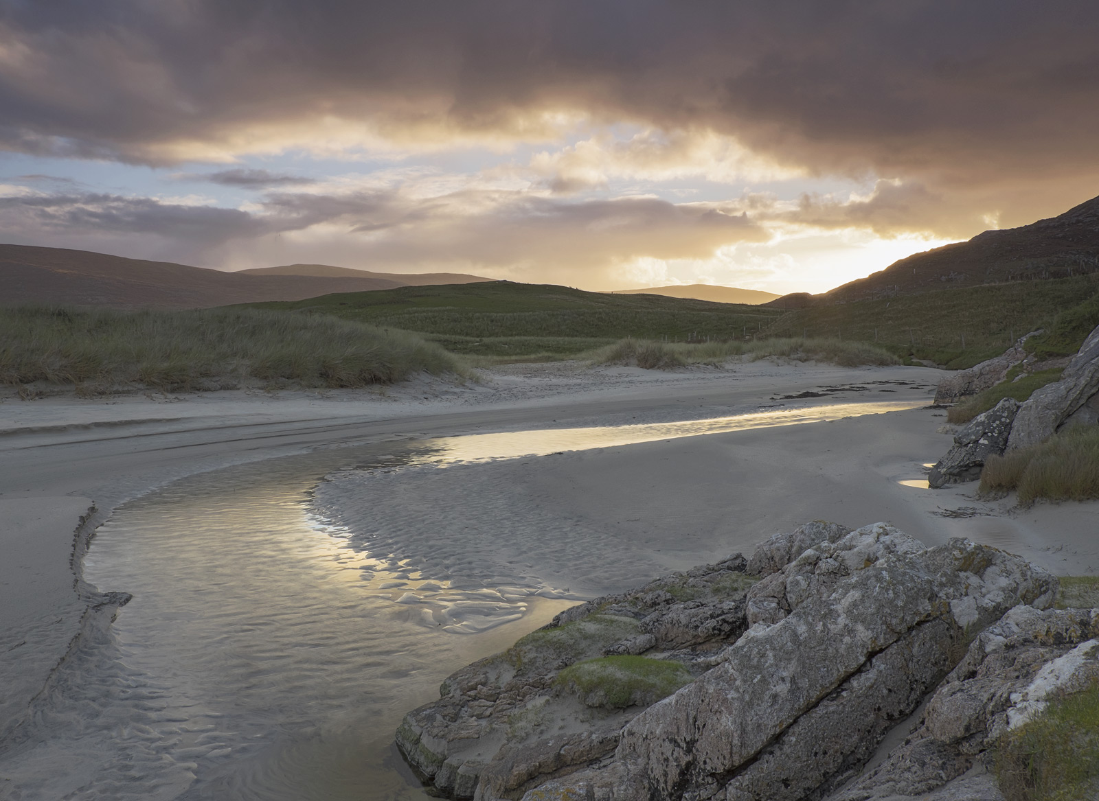 A stream meanders its way to the sea as it filters through the enormous dune backed beach of Seilebost at sunrise, the reflected...