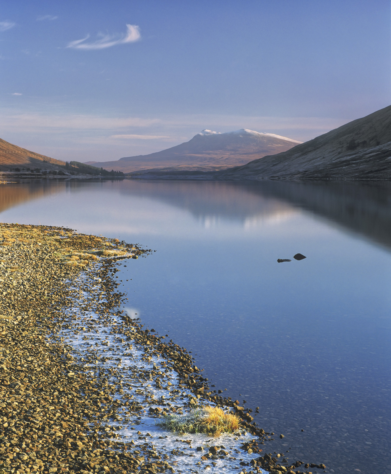 A gorgeous serene and breathlessly still winter morning at the edge of Loch a Chroisg. The weak light of a lemon yellow...