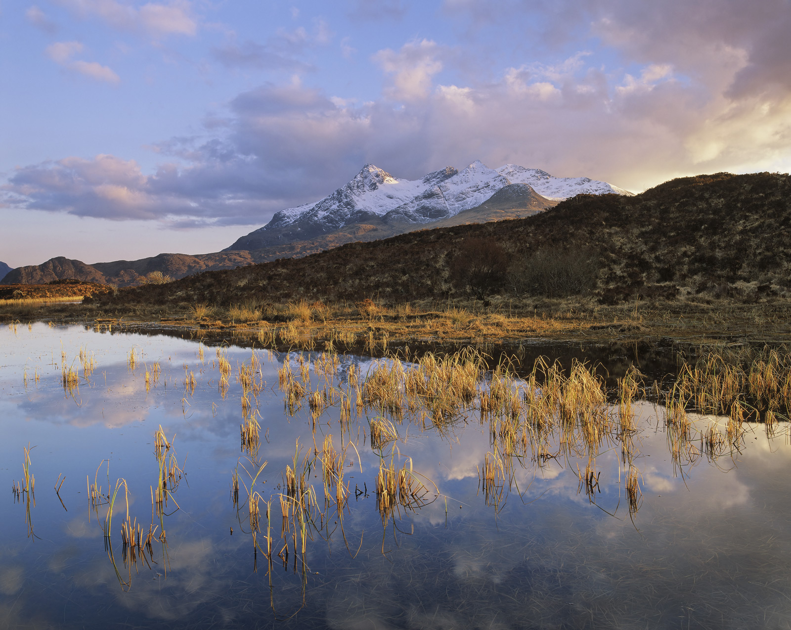 The snow dusted peak of Sgurr Nan Gillean gleams in the late evening sunlight on an Autumnal day. For a brief instant the...