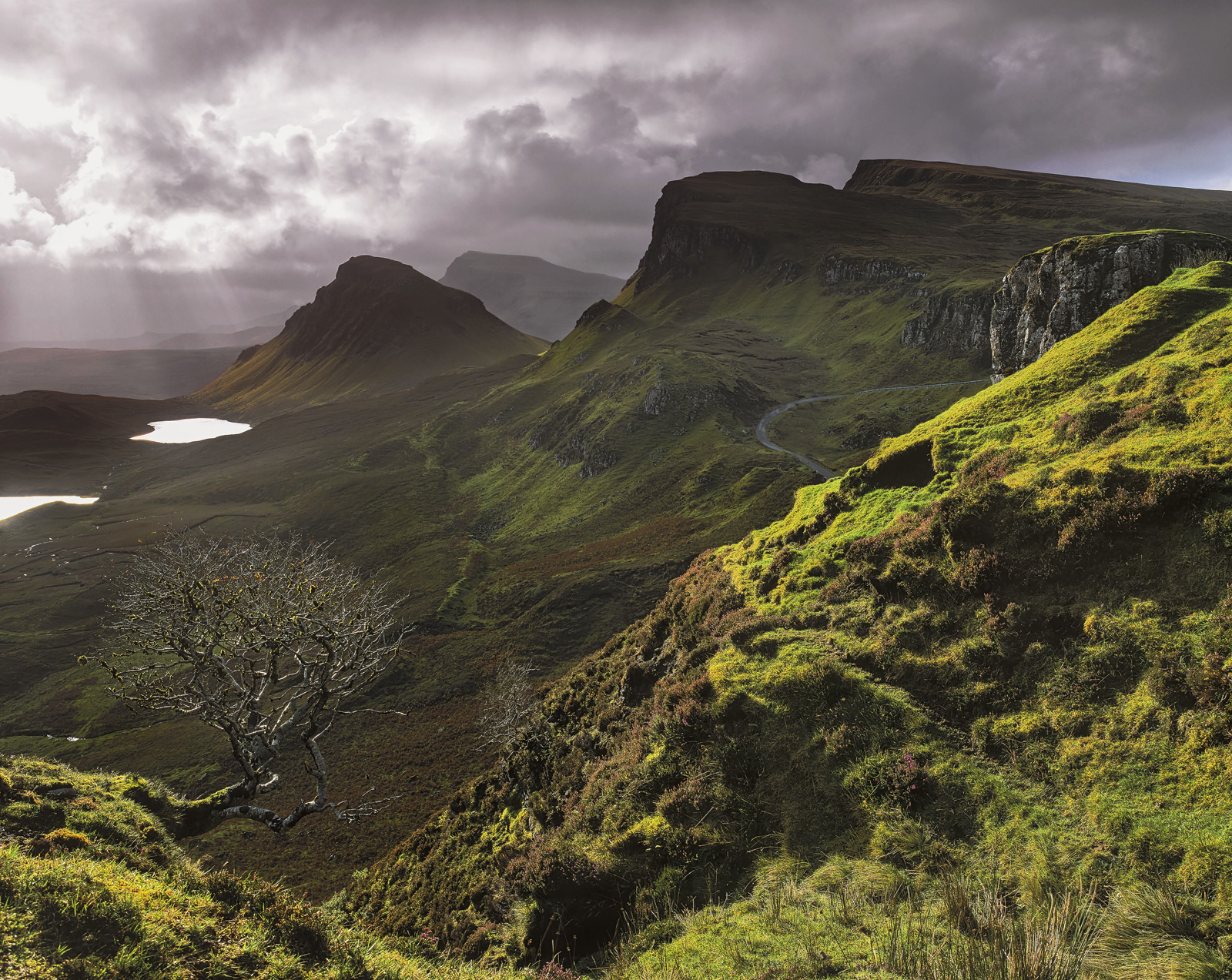 The slopes of the Trotternish ridge at the Quiraing on Skye are lit by a blazing beam of sunlight that scurries across the hills...
