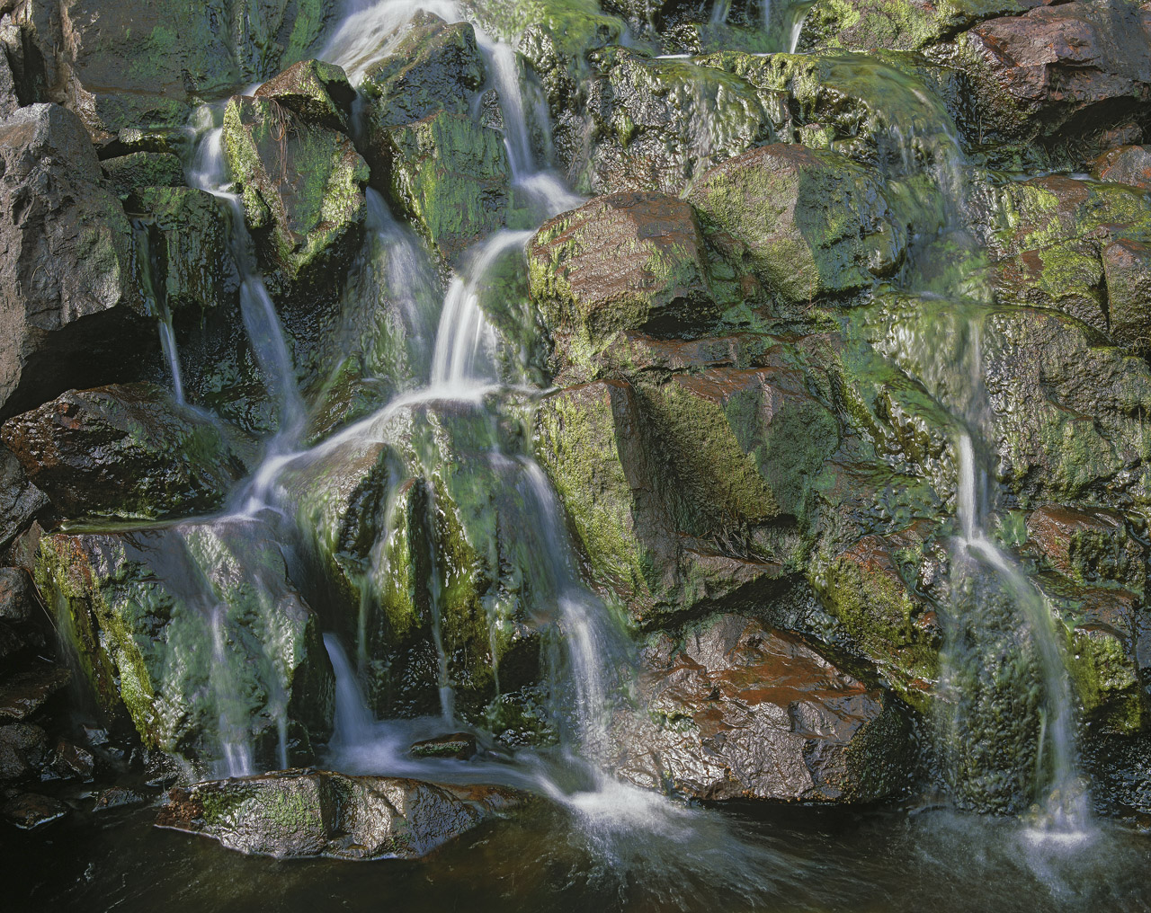A tumbling little cascade descends steeply over a mix of red and grey rocks eventually dropping down to the River Polly.&nbsp...