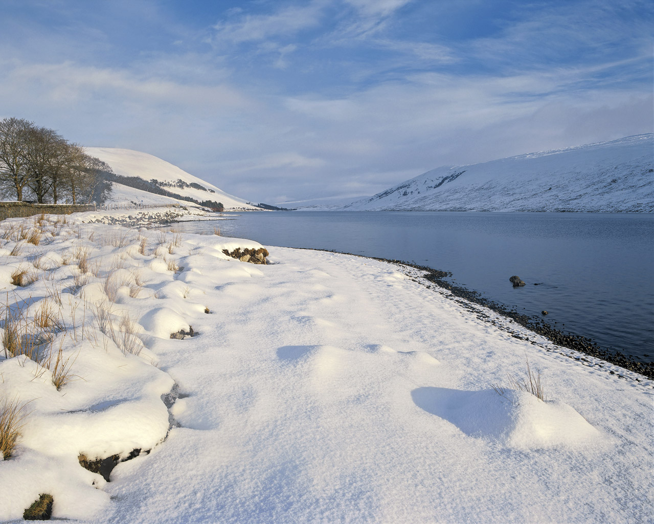 A rare deep and virgin white snow fall coats the shoreline at beautiful but desolate Loch A Chroisg at the gateway to the beautiful...