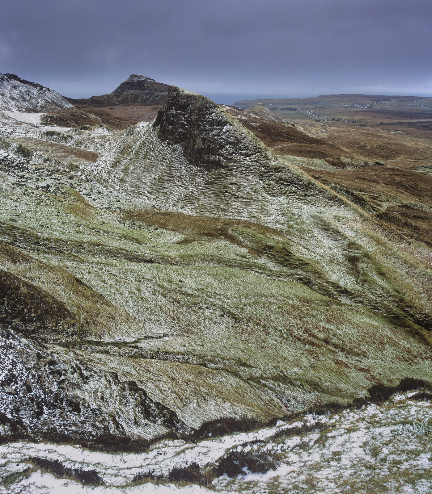 A dusting of high altitude snow barely conceals the colours of the Quiraing beneath and reveals the remarkable texture on the...