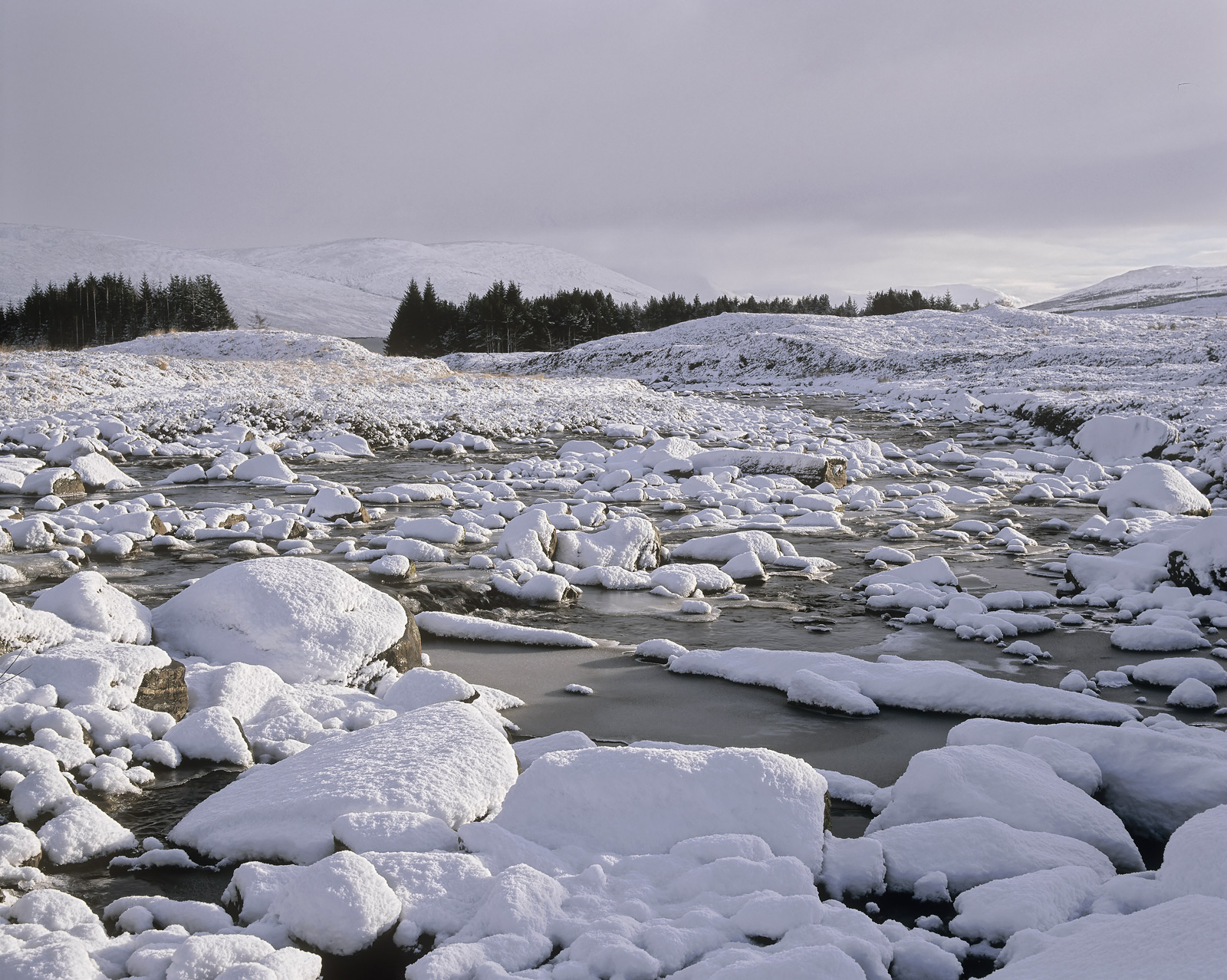 Snow layers the boulders and rocks formingsphericalmounds in the bed of ashallow stream that tumbles down the...