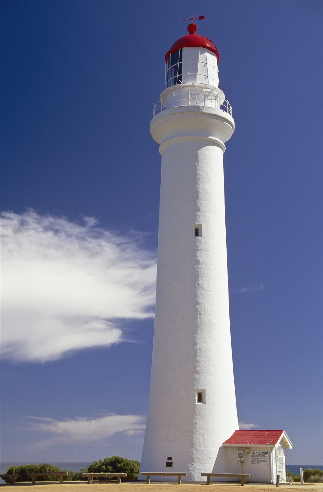 Spit Point Lighthouse is a pristine white tower with an attached entrance shed complete with red roofs on both the lamp housing...