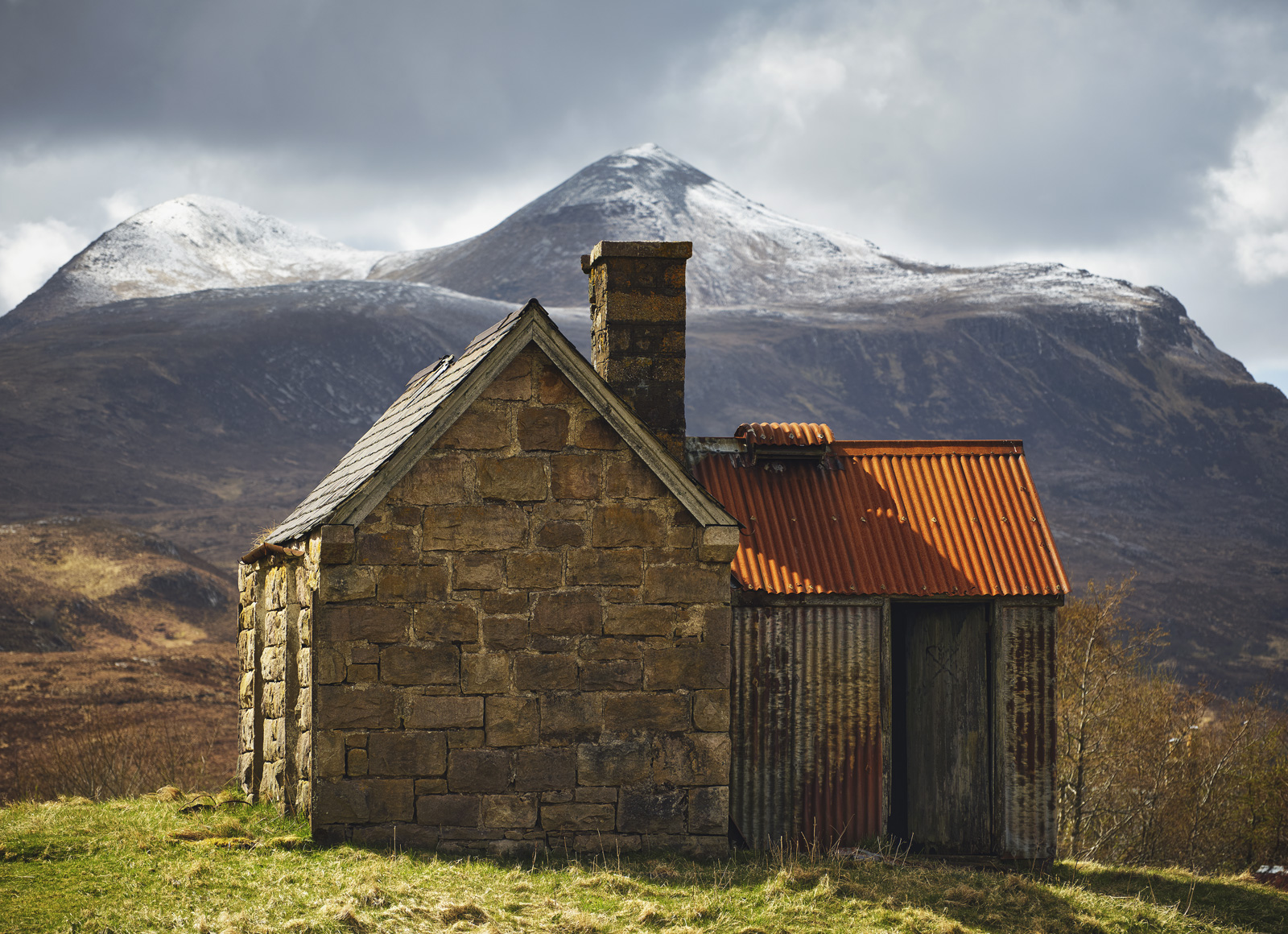 Elphins little decrepit shack on a grassy knoll makes a compelling subject against snow capped Cul Mor in Elphin