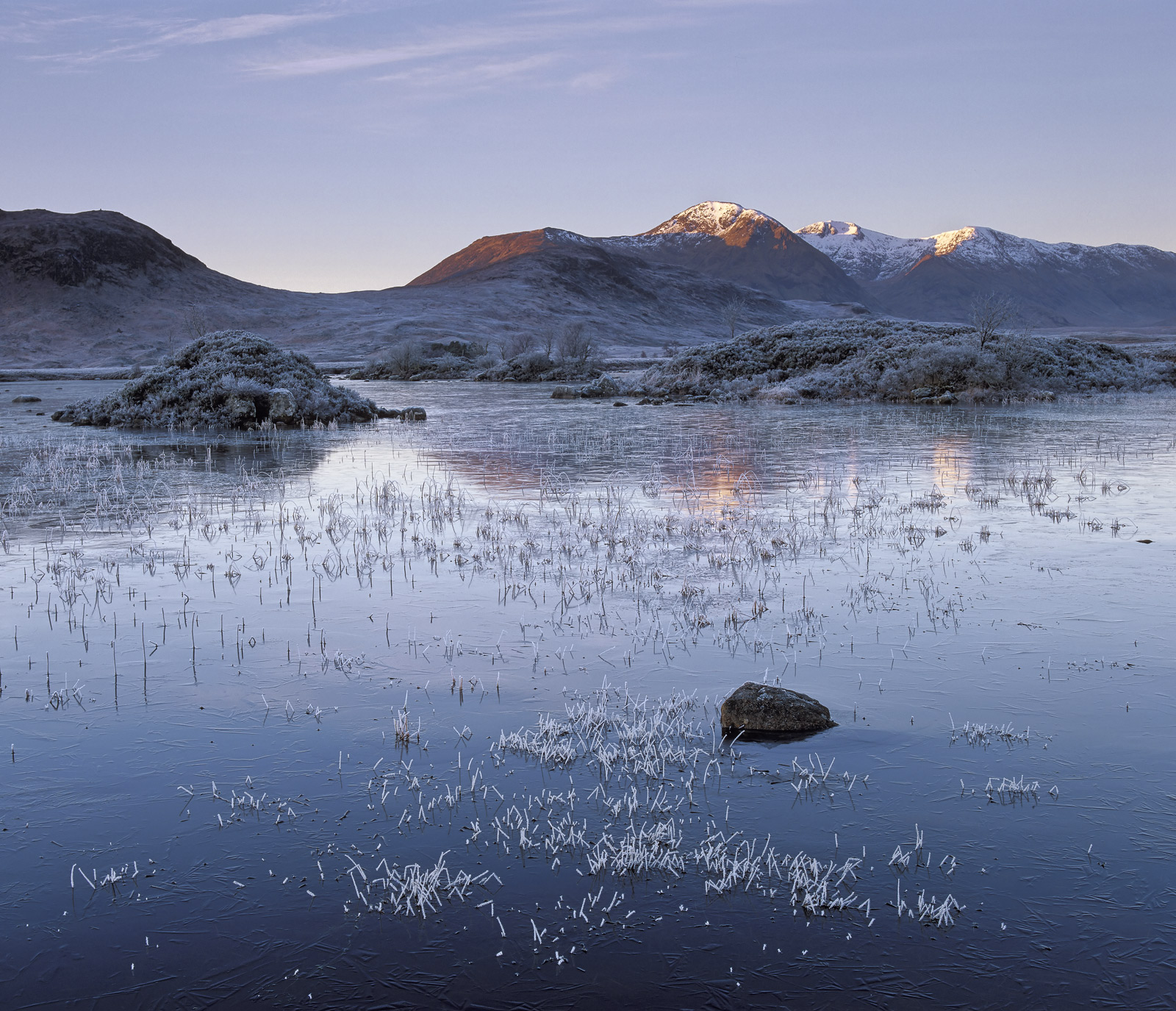 Steel blue ice on a frosty winter morning freezes over the lochans on Rannoch moor and then the first red rays of sunlight strike...