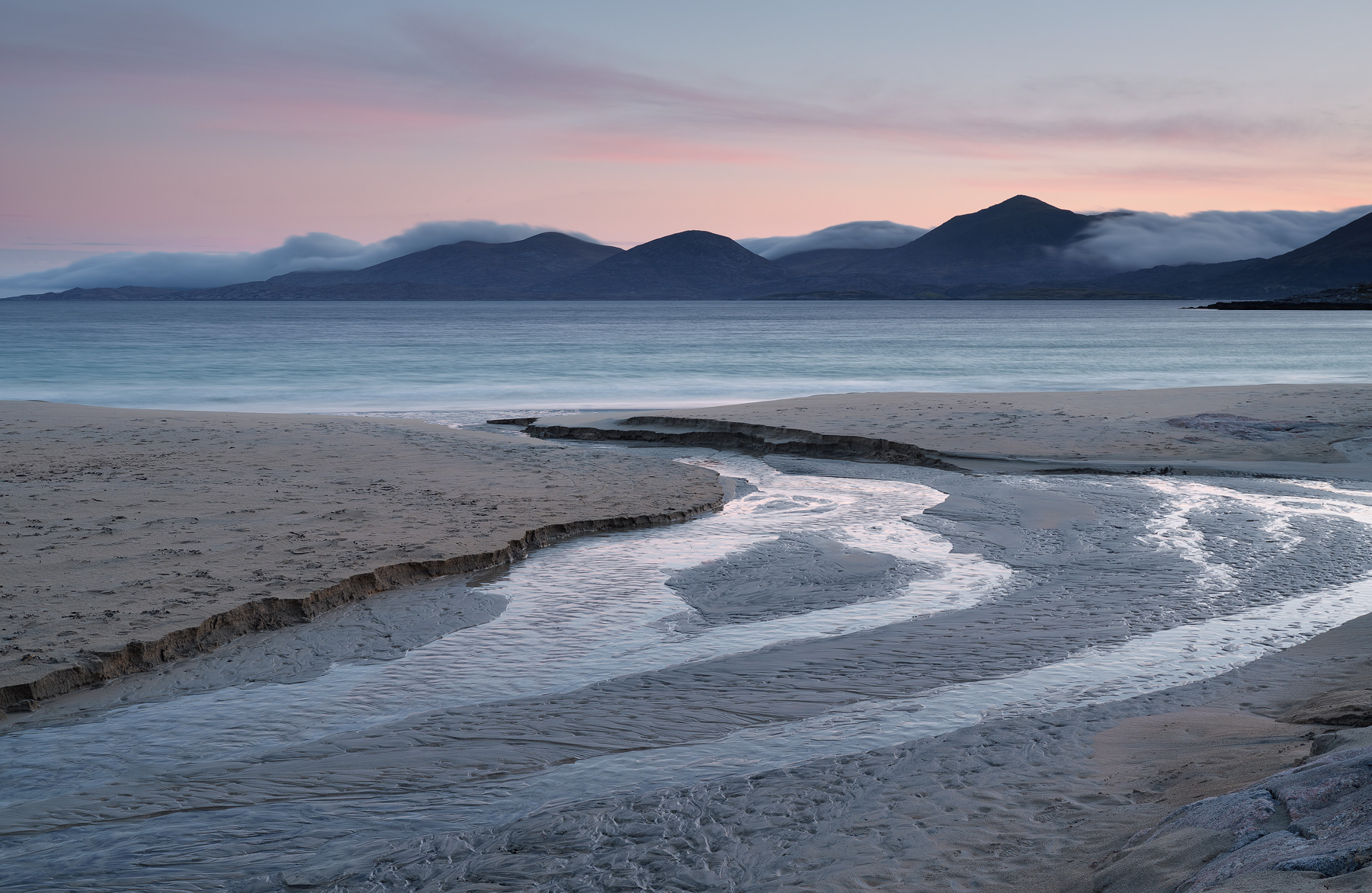 A meandering peat stream cuts through the dunes and carves a fresh path through soft sand on its way to the beach at Traigh Rosamol on Harris