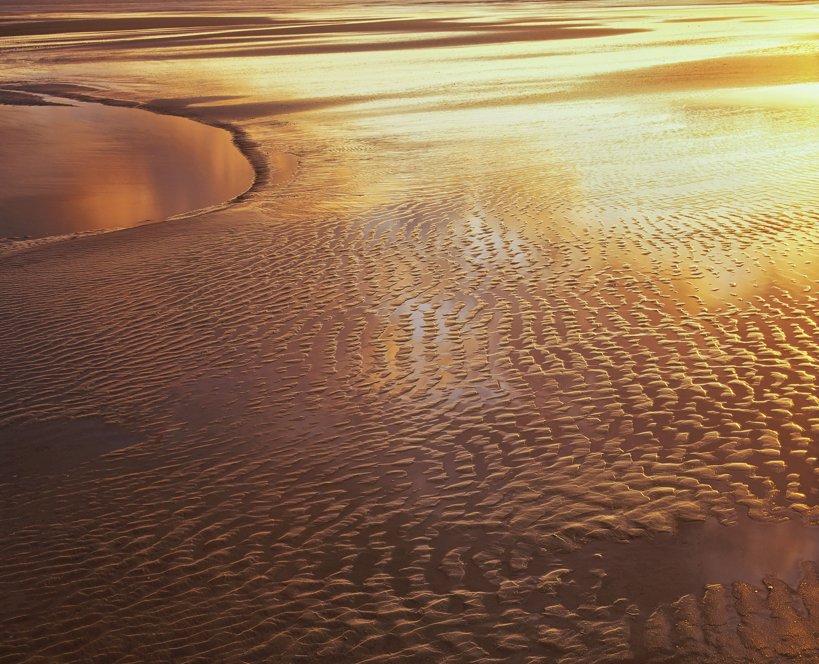 A perfectly beautiful stippled and patterned section of Findhorn Bay reflecting a golden sunset onto its still surface in a most...