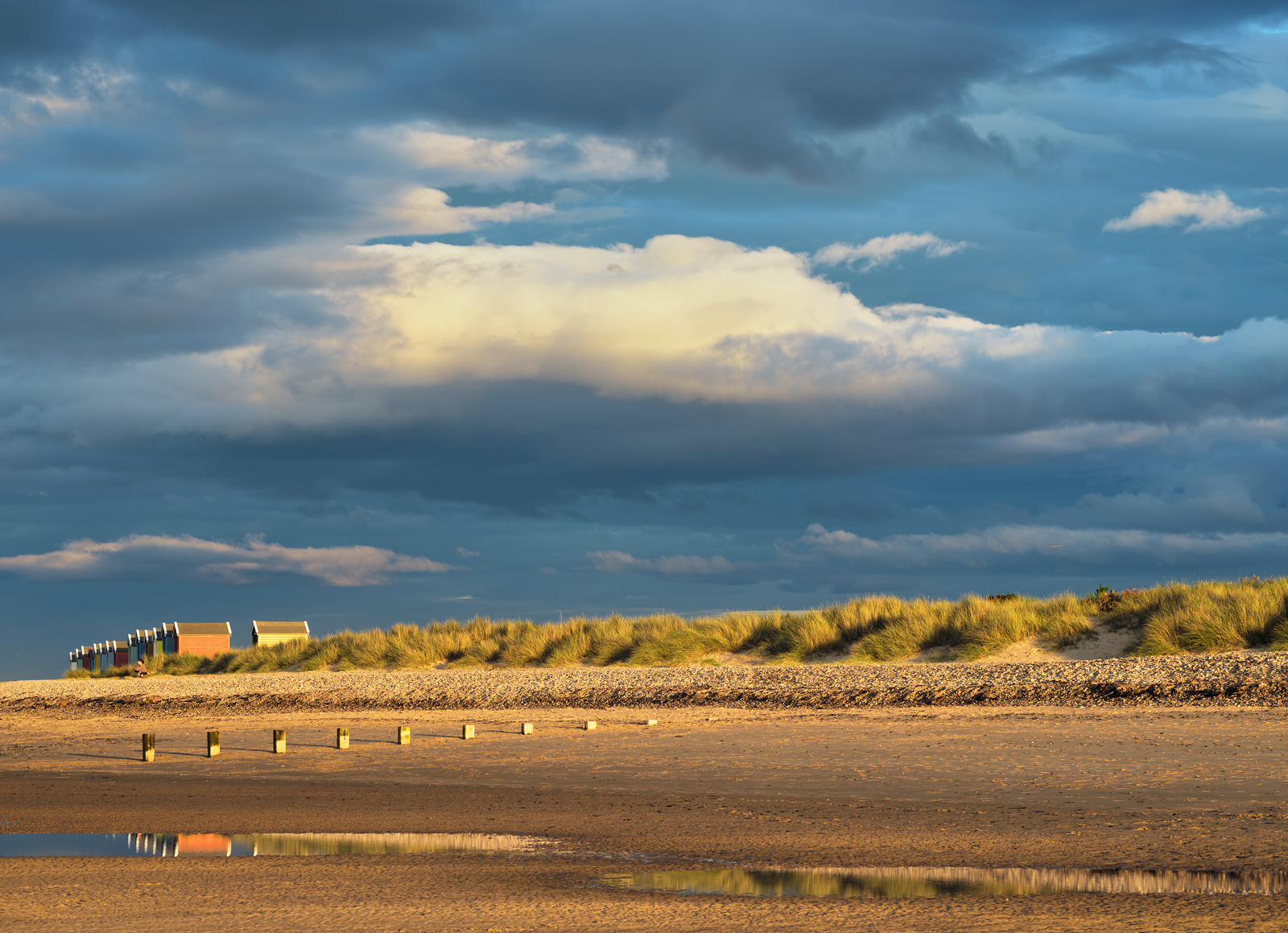 Golden sunlight streams through the clouds close to sunlight spot lighting the Findhorn huts beach and dunes whilst an epic moody sky glowers down from above.