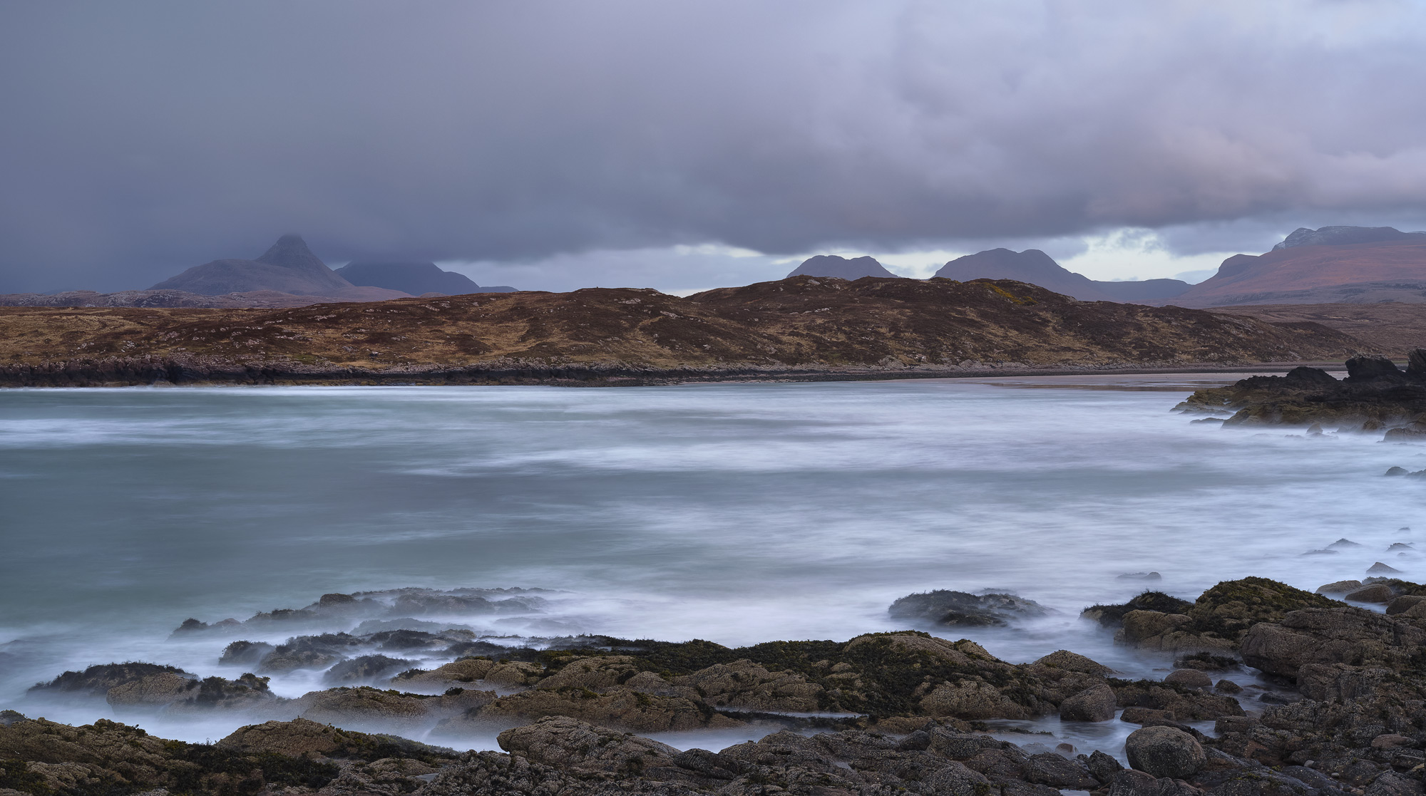 Stormy skies and rolling waves crash into the rocky coast bordering beautiful sandy Achnahaird Bay just before sunset in the Inverpolly reserve.