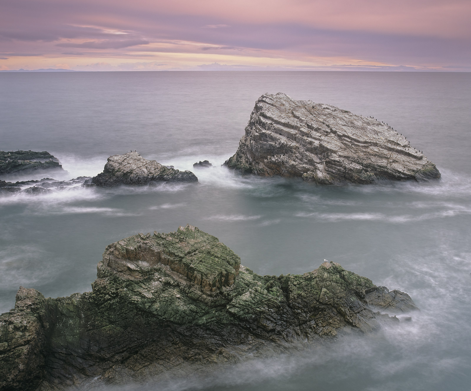 A pink sky slowly melted into the grey clouds that hung over the Moray Firth so I photographed the impressively angular rocks...