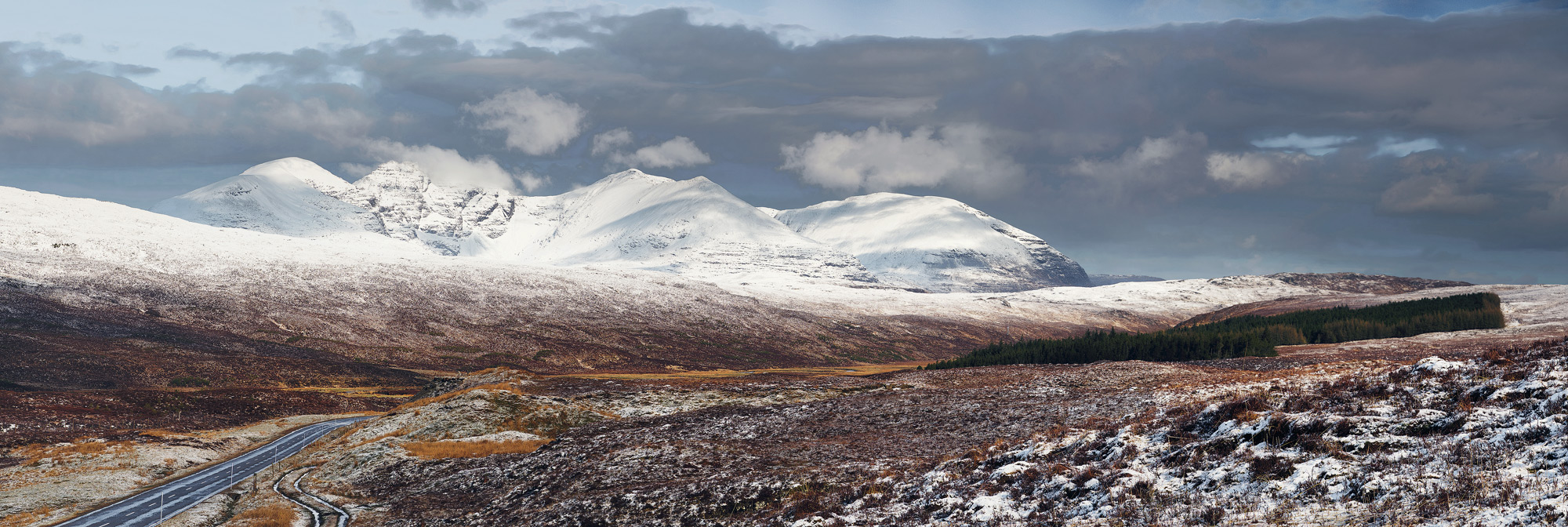 Sunlit and snow clad An Teallach between Braemore Junction and Dundonnell appeared brilliant white with patches of light and shade above the moorland plateau