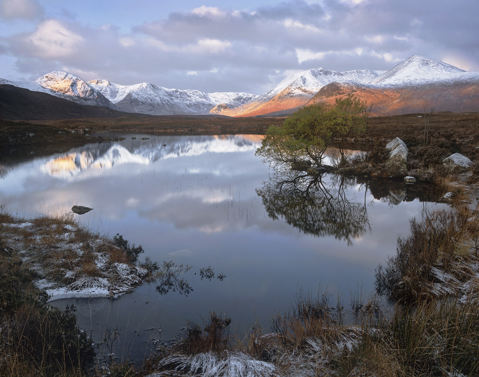 Sunrise over Rannoch moor on a windless morning with new snow ladled over the distant Blackmount. At first light, sunlight...