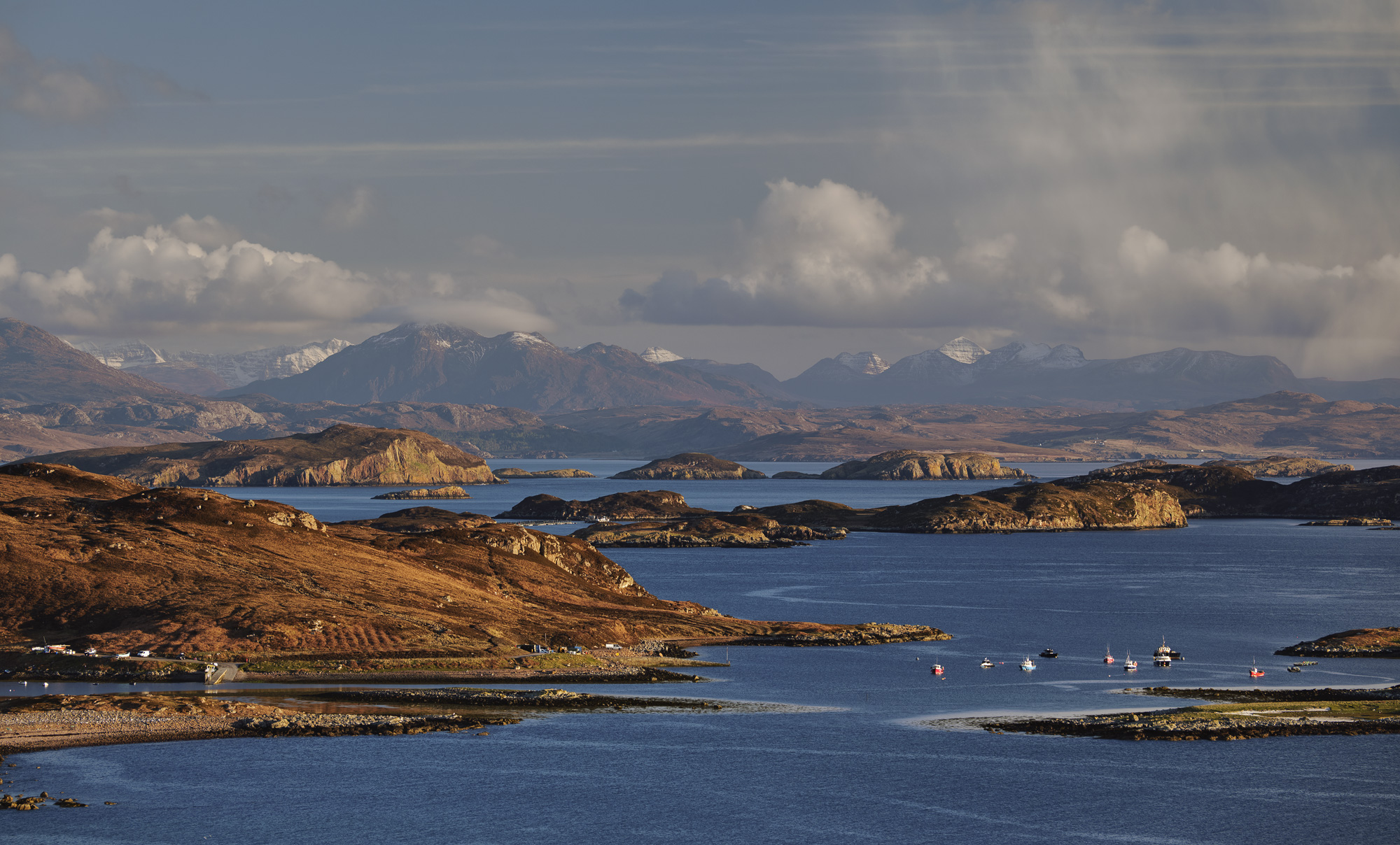 The Summer Isles a collection of low lying islands captured in golden late afternoon Spring sunlight from the high viewpoint near Reiff.