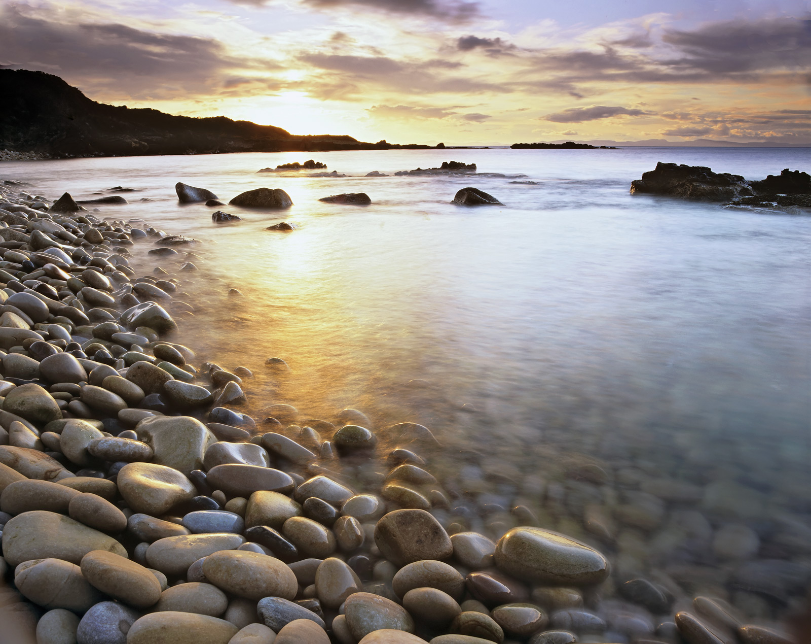 A sweep of soft ball sized pebbles pale in colour plunges down into the clear waters of the Moray Firth. The tide laps...