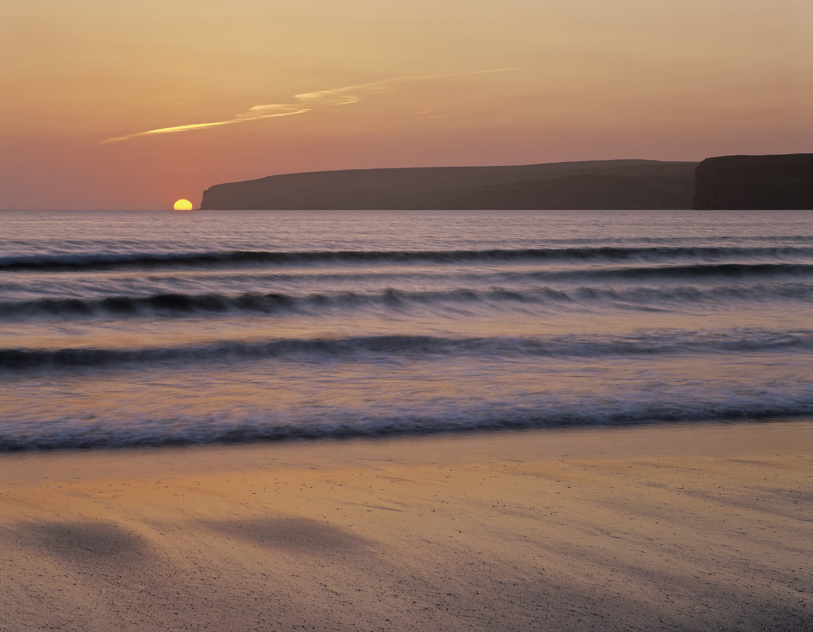 A tangerine sun sinks through a soft sea haar and crashes into the sea by the Dunnet Head cliffs on a relaxing and very pleasant...